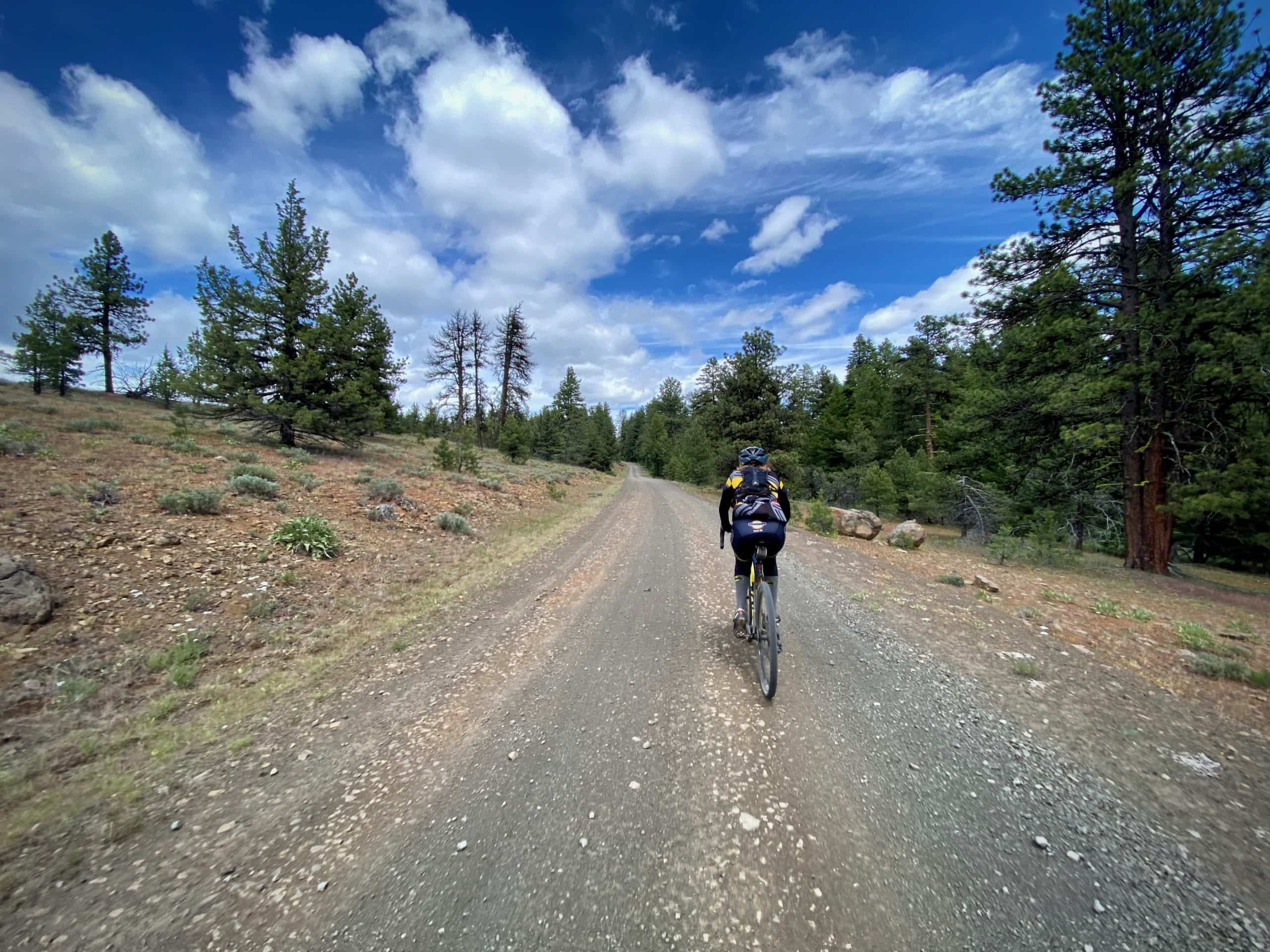 Gravel Girl riding through a red lava flow in the Ochoco Mountains near Mitchell, Oregon.