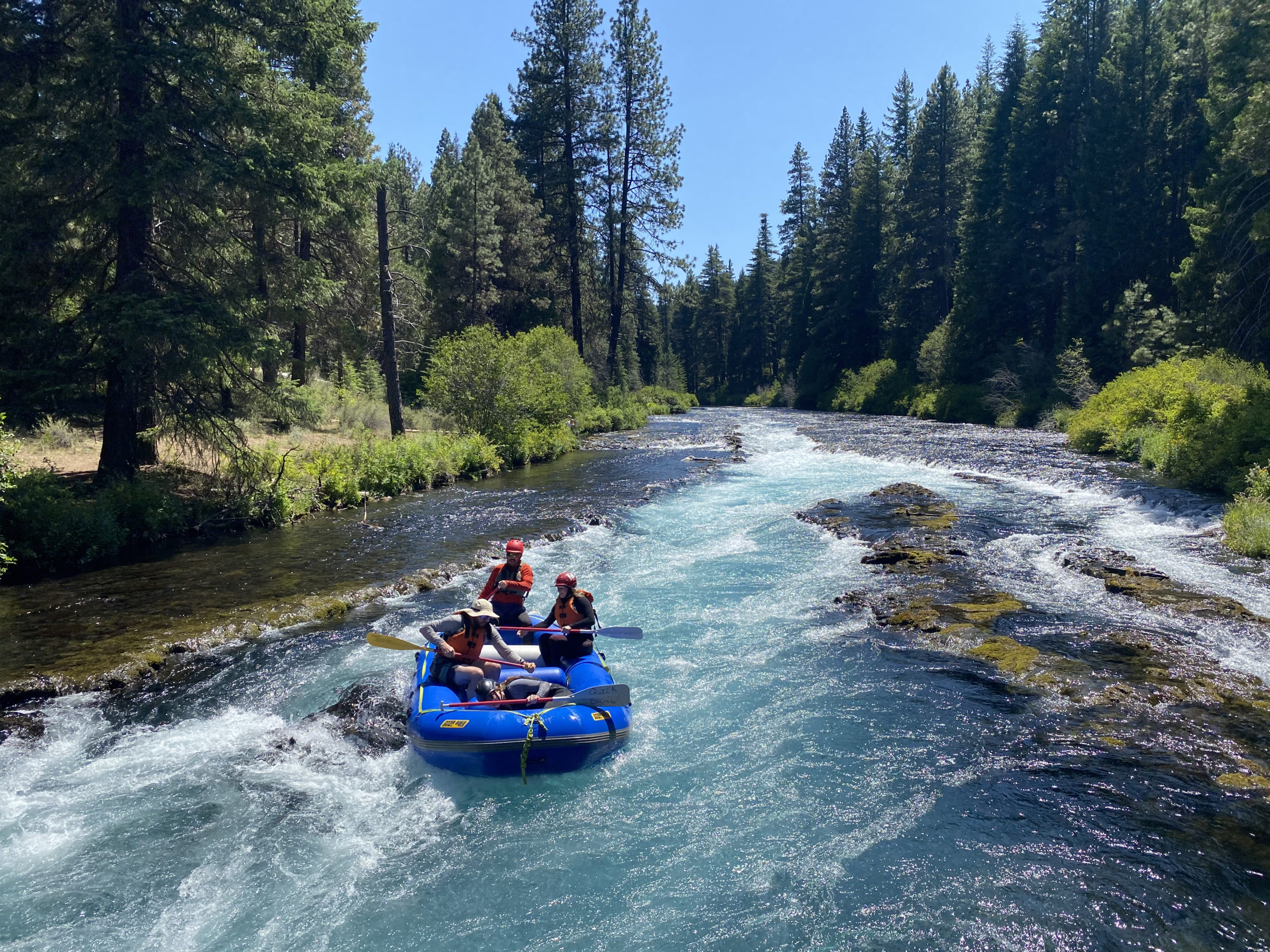 Rafters going underneath the vehicle bridge at Wizard Falls fish hatchery on the Metolius River.