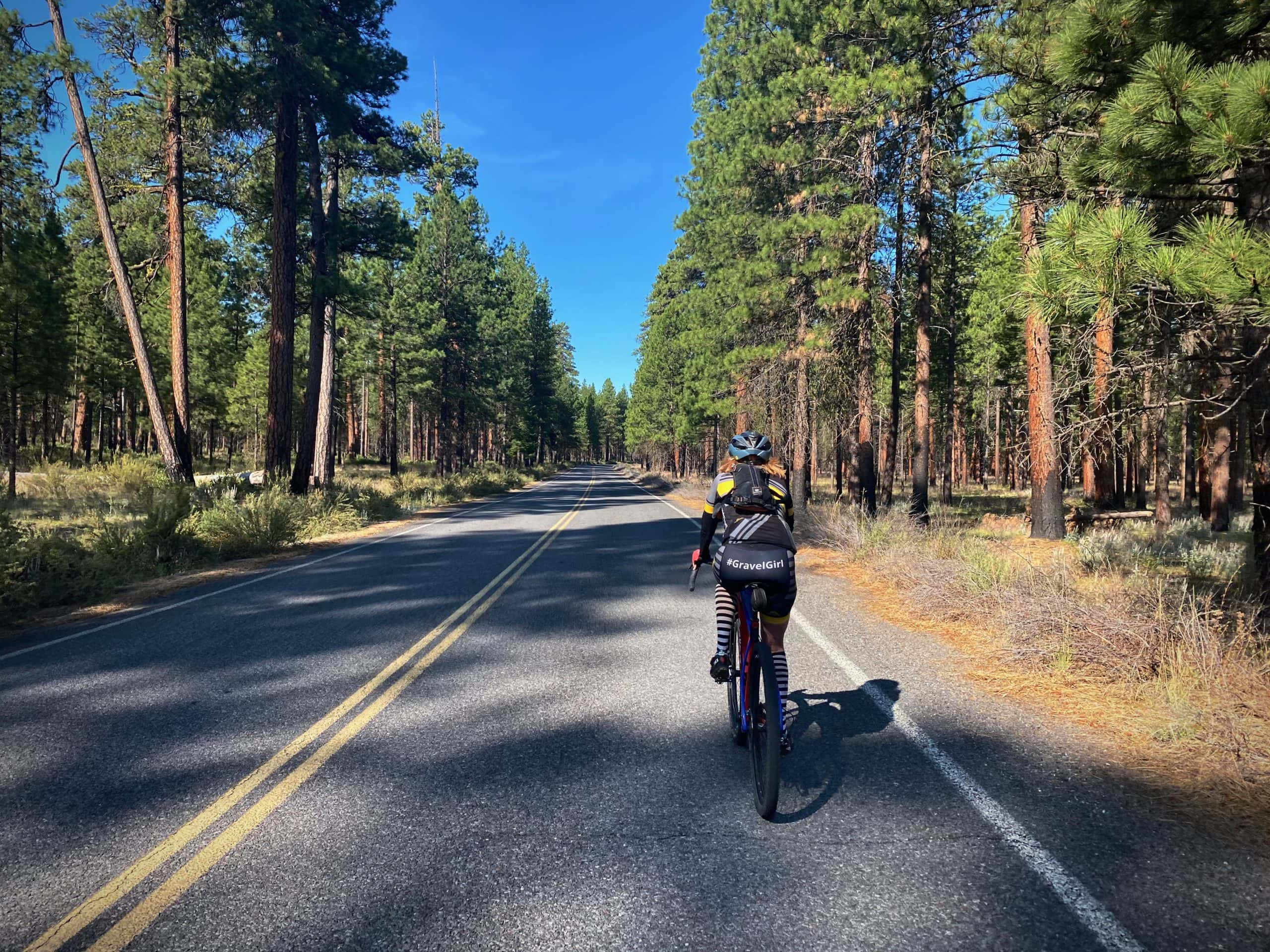 Bike rider on paved road near the Head of the Metolius in Camp Sherman, Oregon.