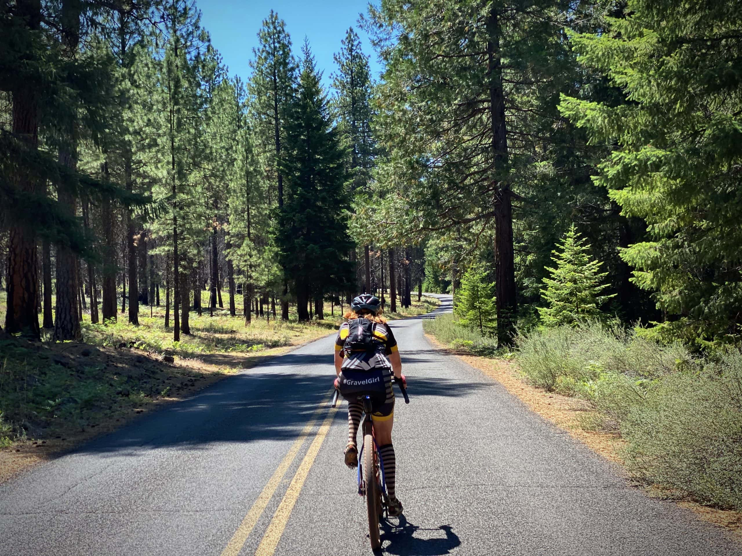 Woman cyclist riding NF 14, paved two-lane road, nearing the Wizard Falls fish hatchery.