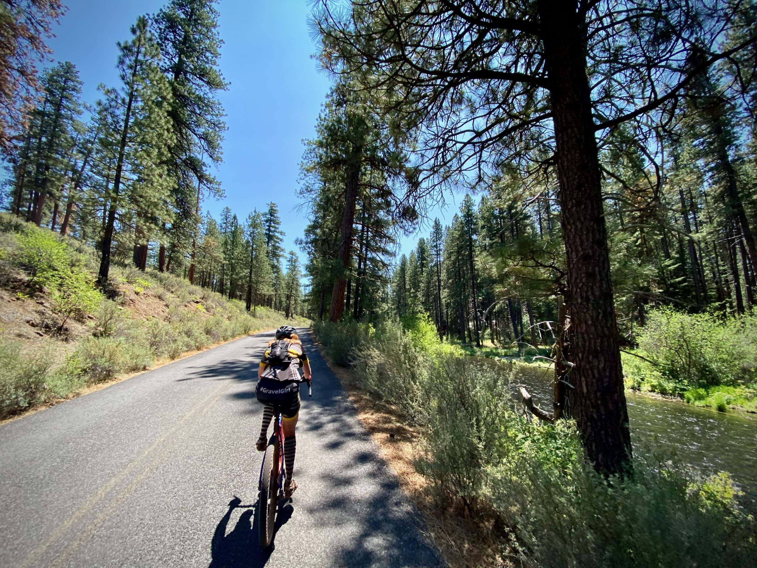 Cyclist riding the SW Metolius River road with the Metolius River to the right.