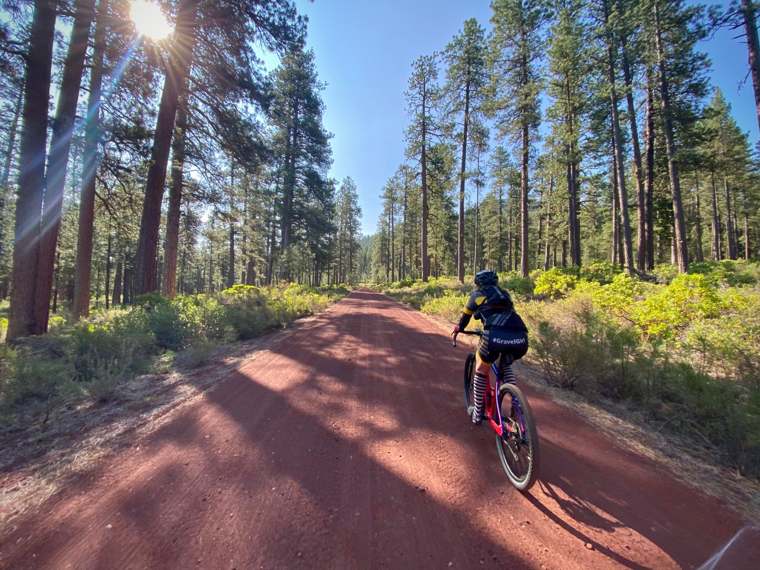 Gravel cyclist on red cinder road on the north shoulder of Black Butte.