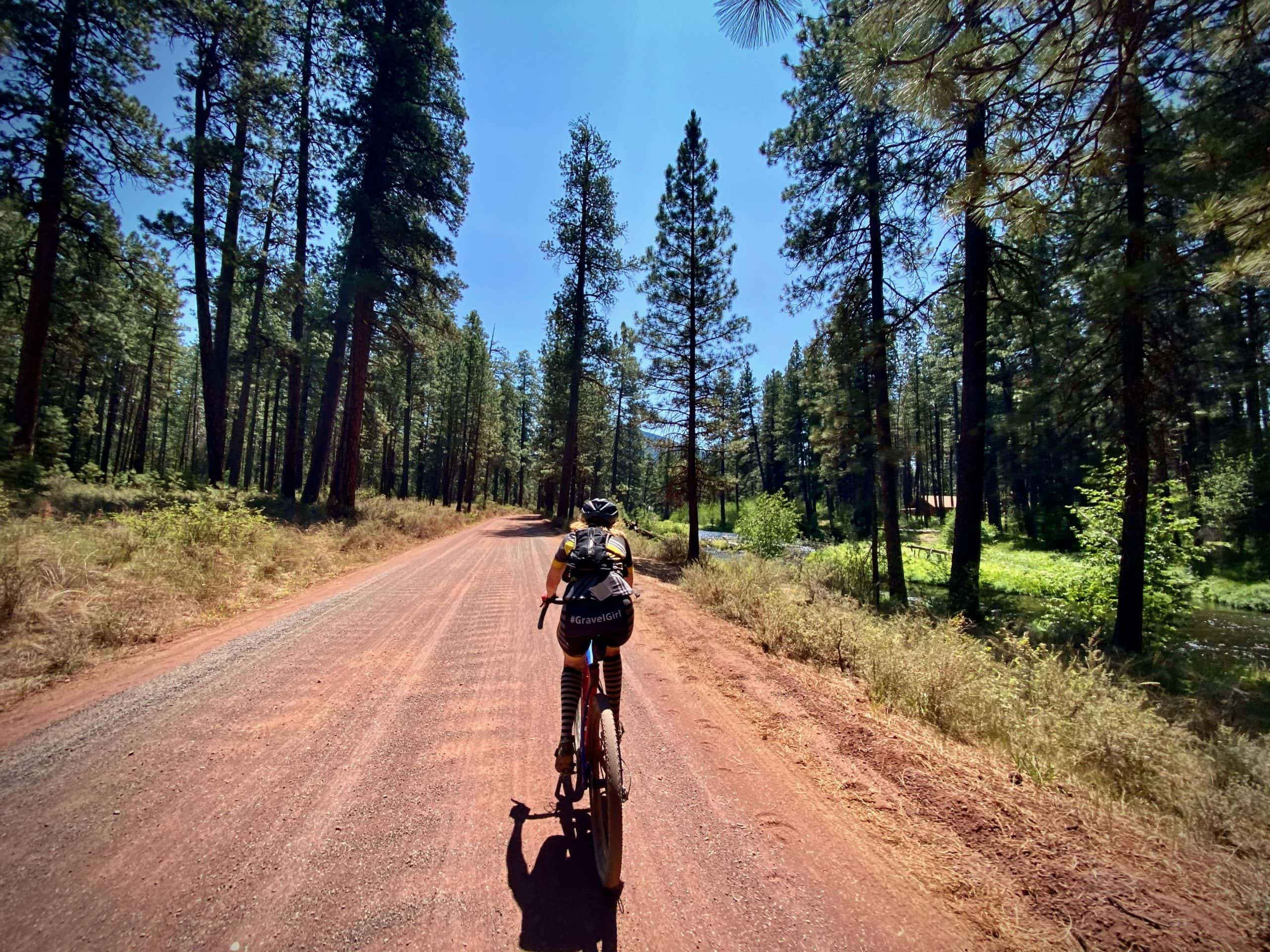 Gravel cyclist on red cinder road leading south from the Camp Sherman General Store.