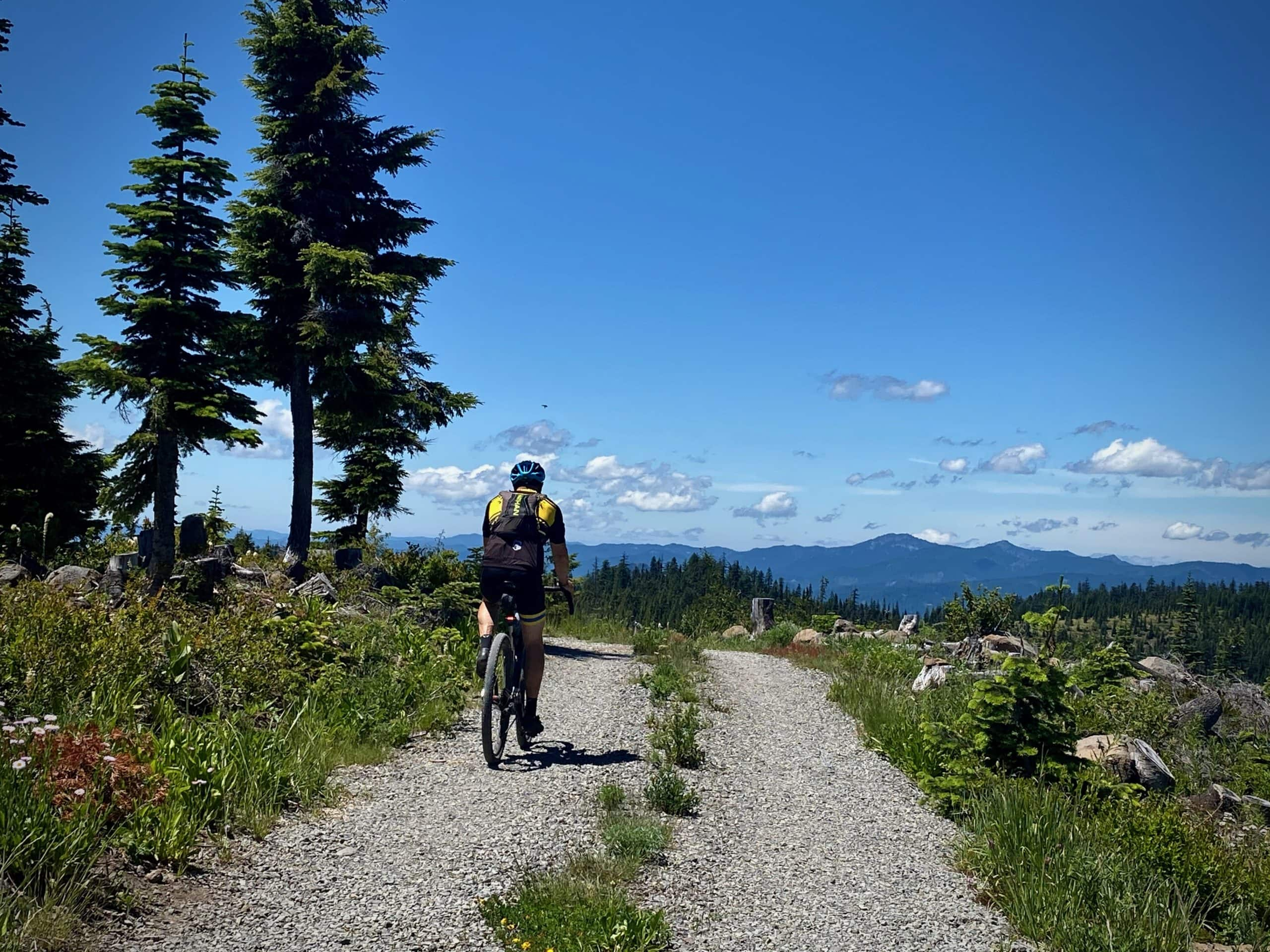 Cyclist leaving the Warner Ridge Lookout on gravel road.