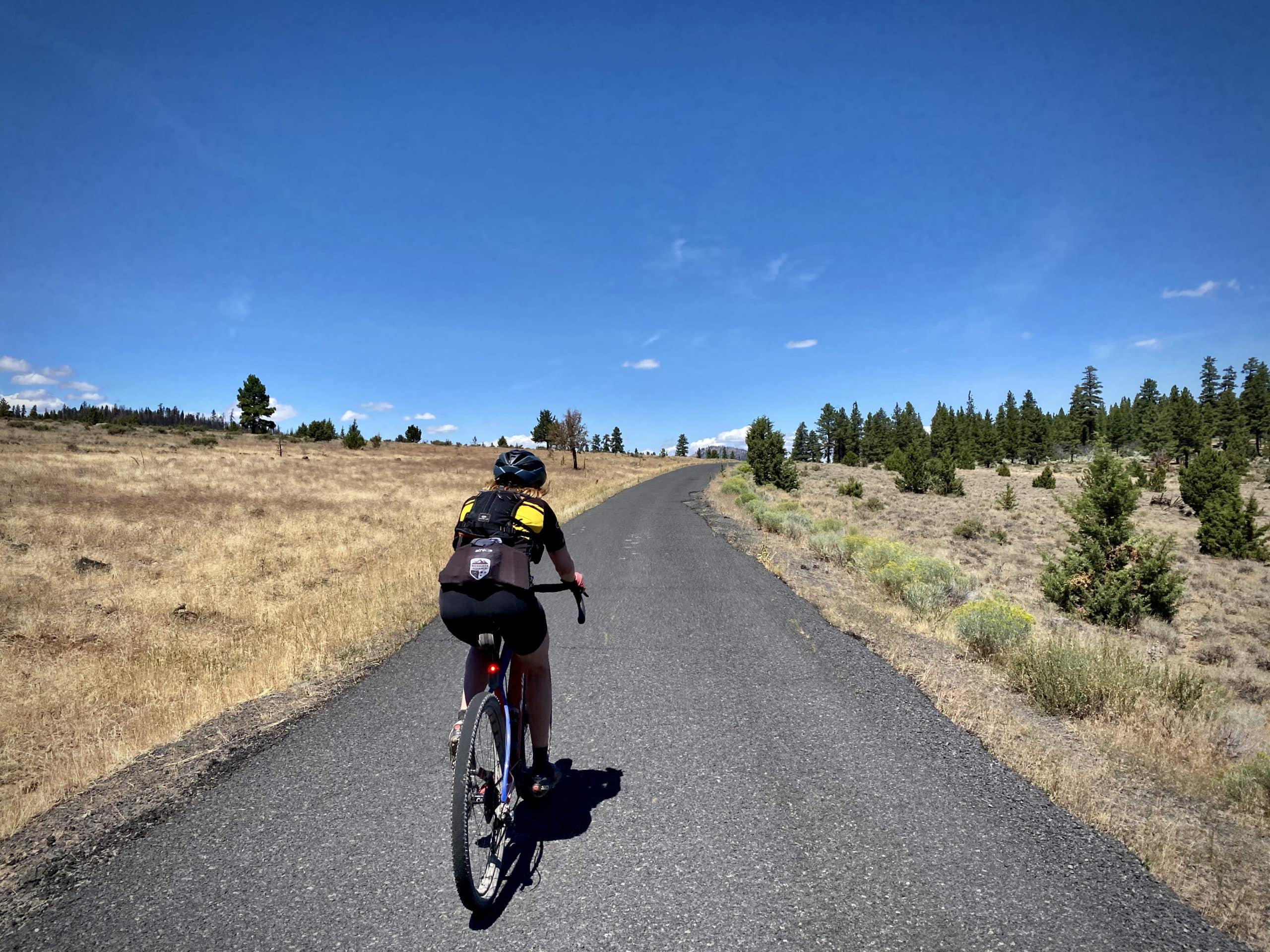 Cyclist on paved road NF 33 near Paisley, Oregon.