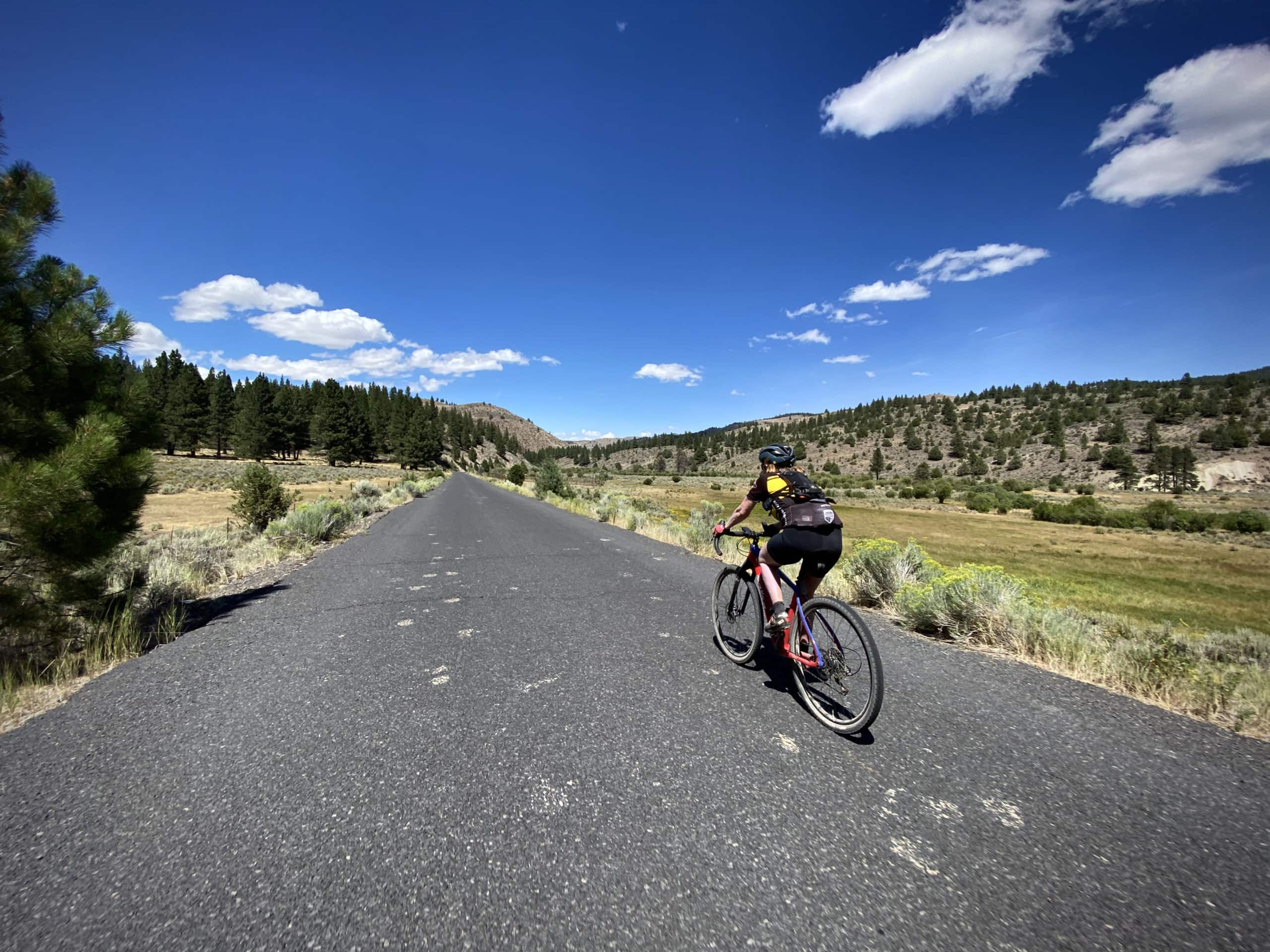 Cyclist on paved road near Coffee Pot Flat in Paisley, Oregon.