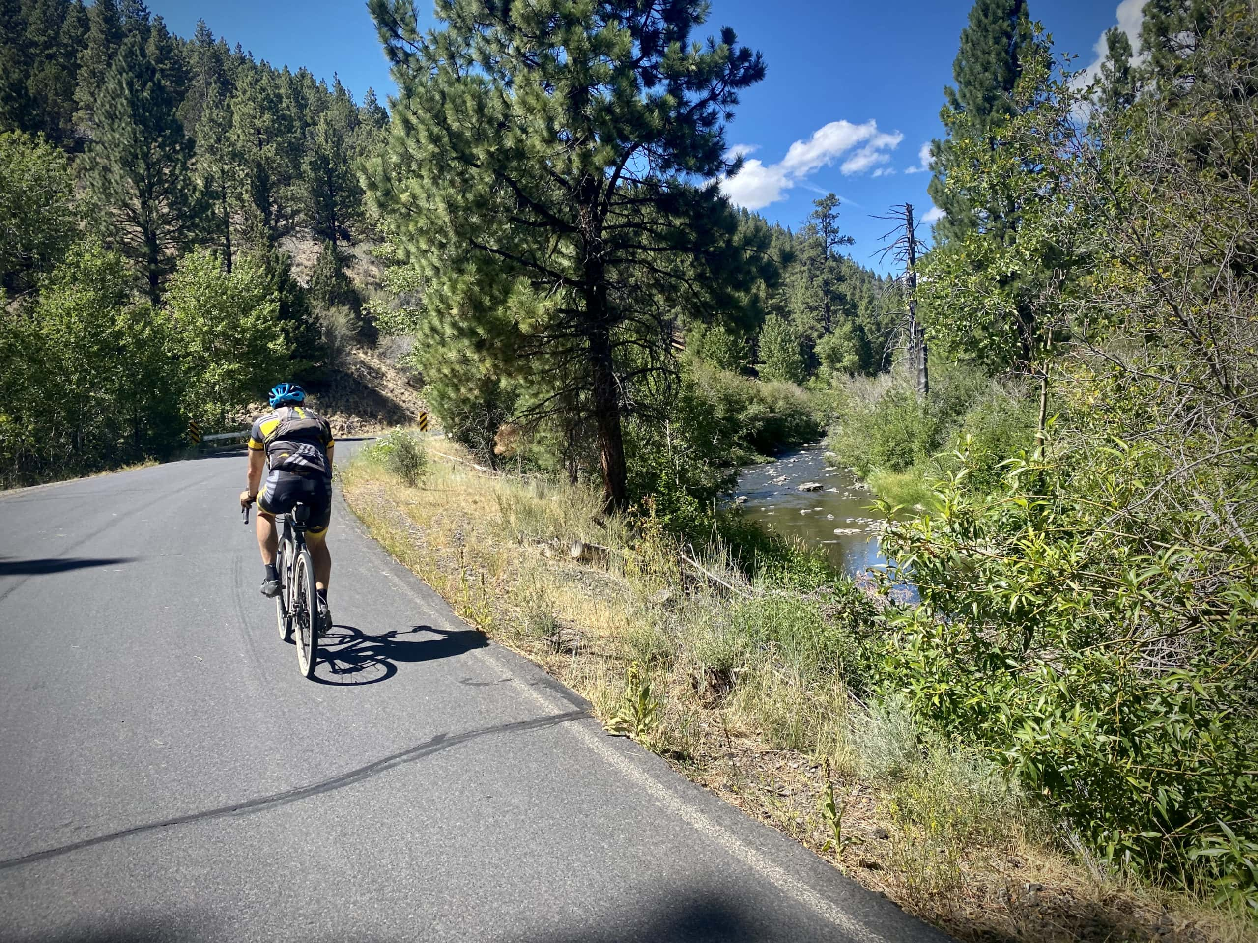 Cyclist riding next to Chewaucan River in Lake County, Oregon.