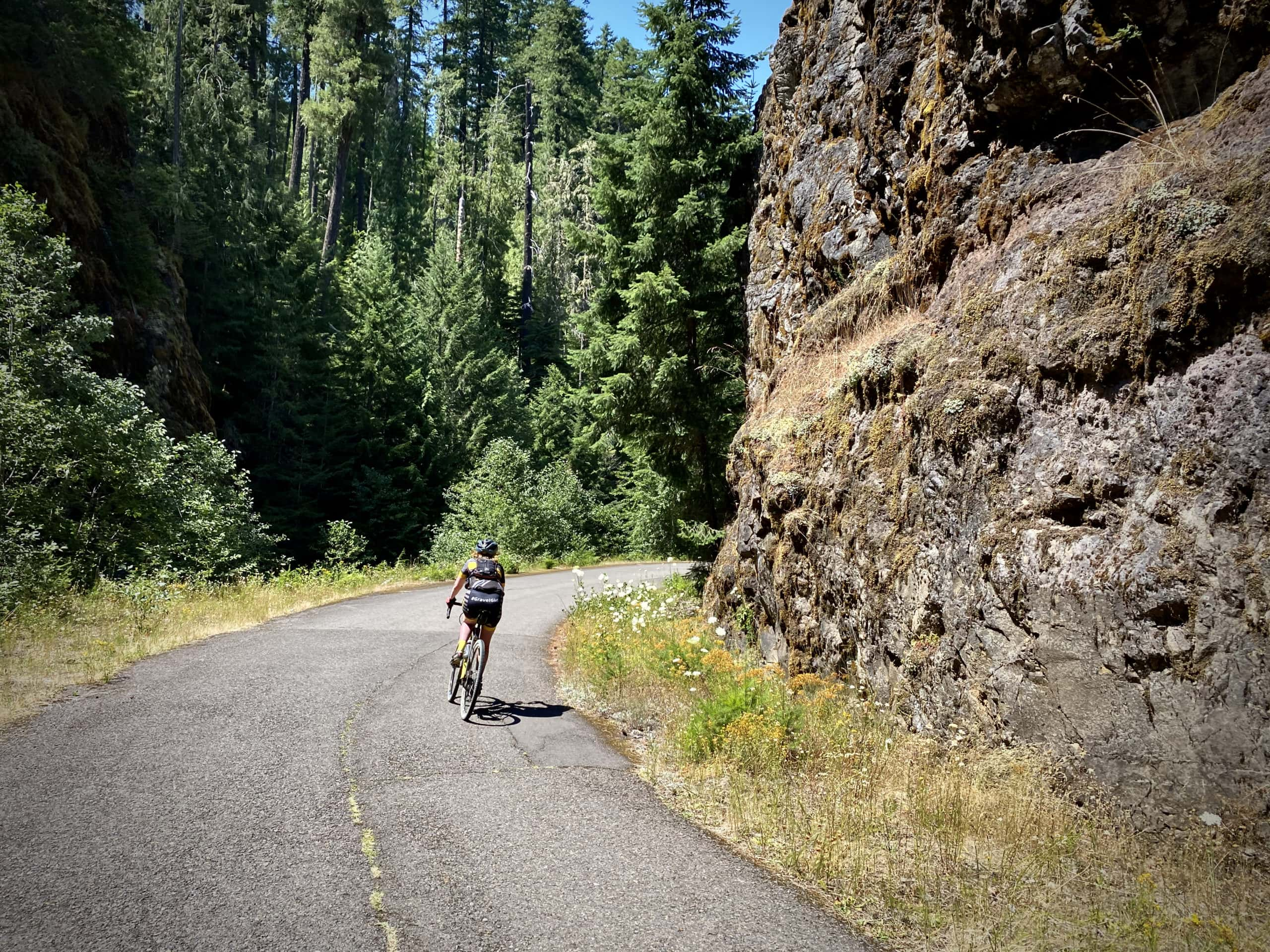 Cyclist on NF 23 going around a right hand corner with rock wall to right. Near Oakridge, Oregon.