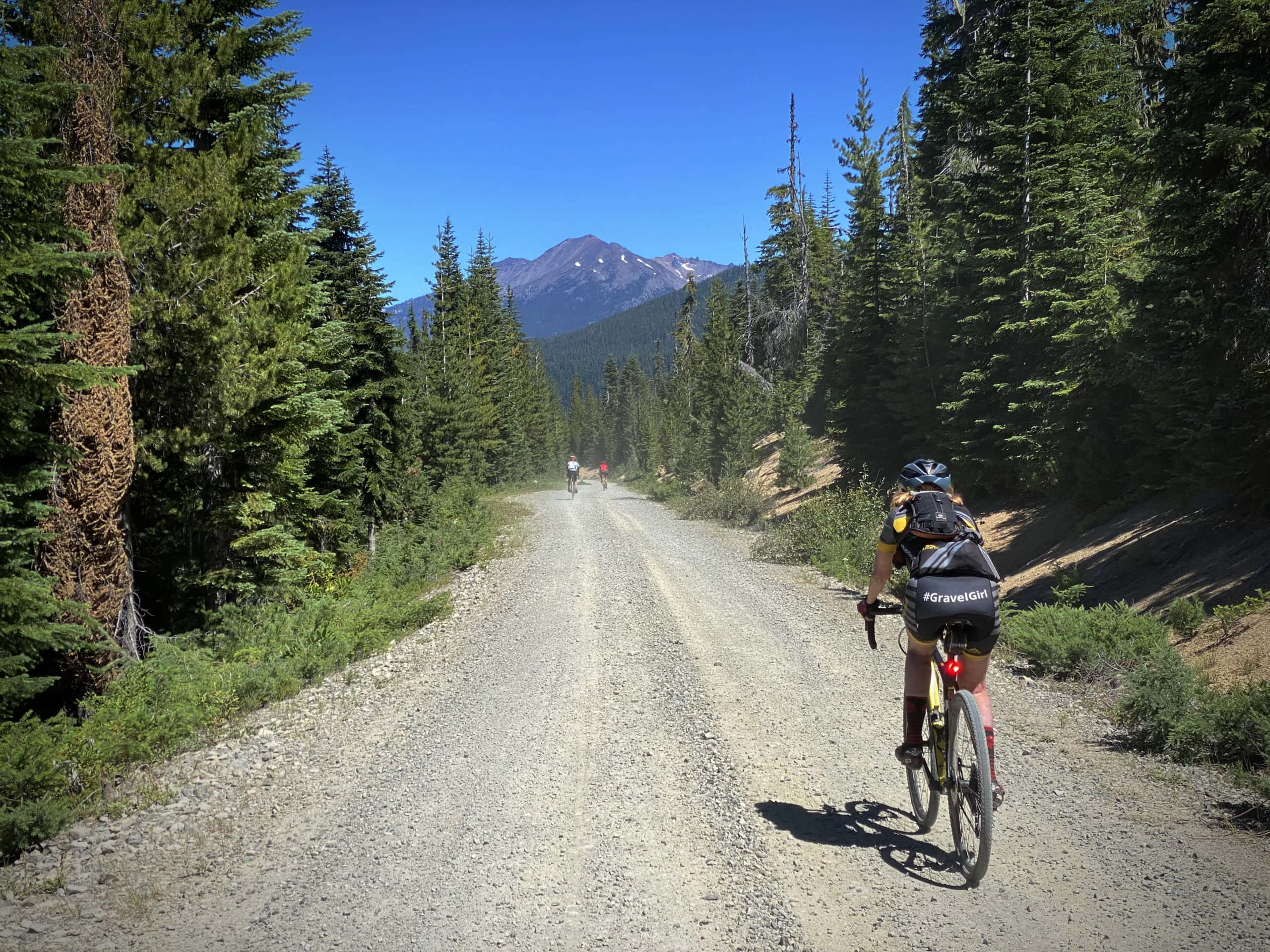Cyclists riding downhill on gravel road with Diamond Peak in distance.