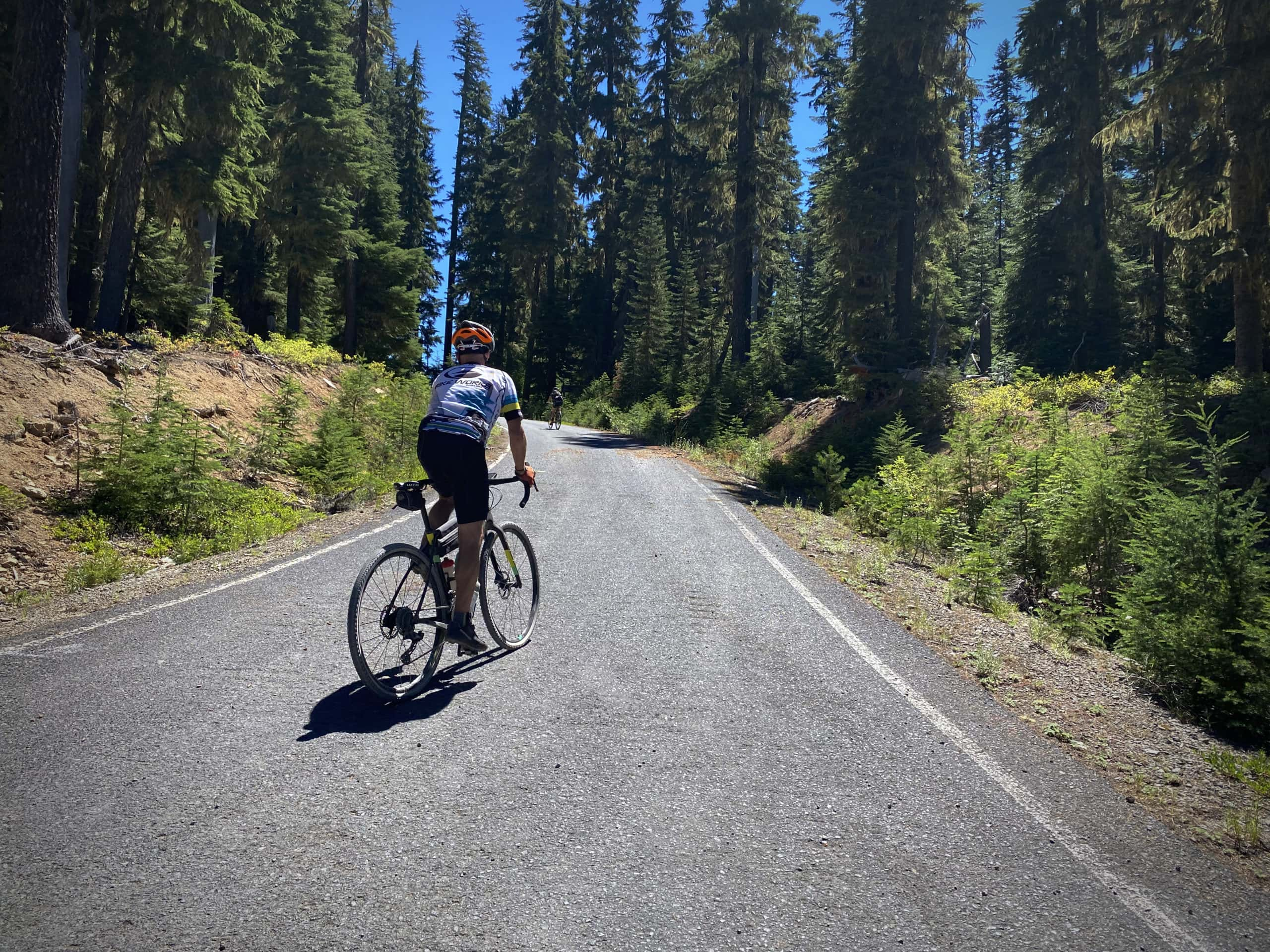 Cyclists making turn from gravel road to paved road in the North Umpqua National Forest.