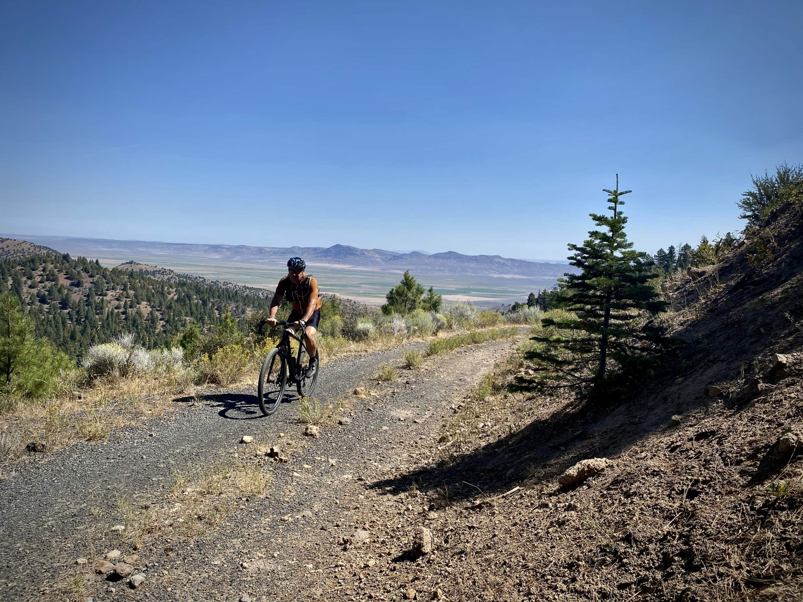 Cyclist on gravel road with views back to the east of Abert Lake and the Hart Mountains.