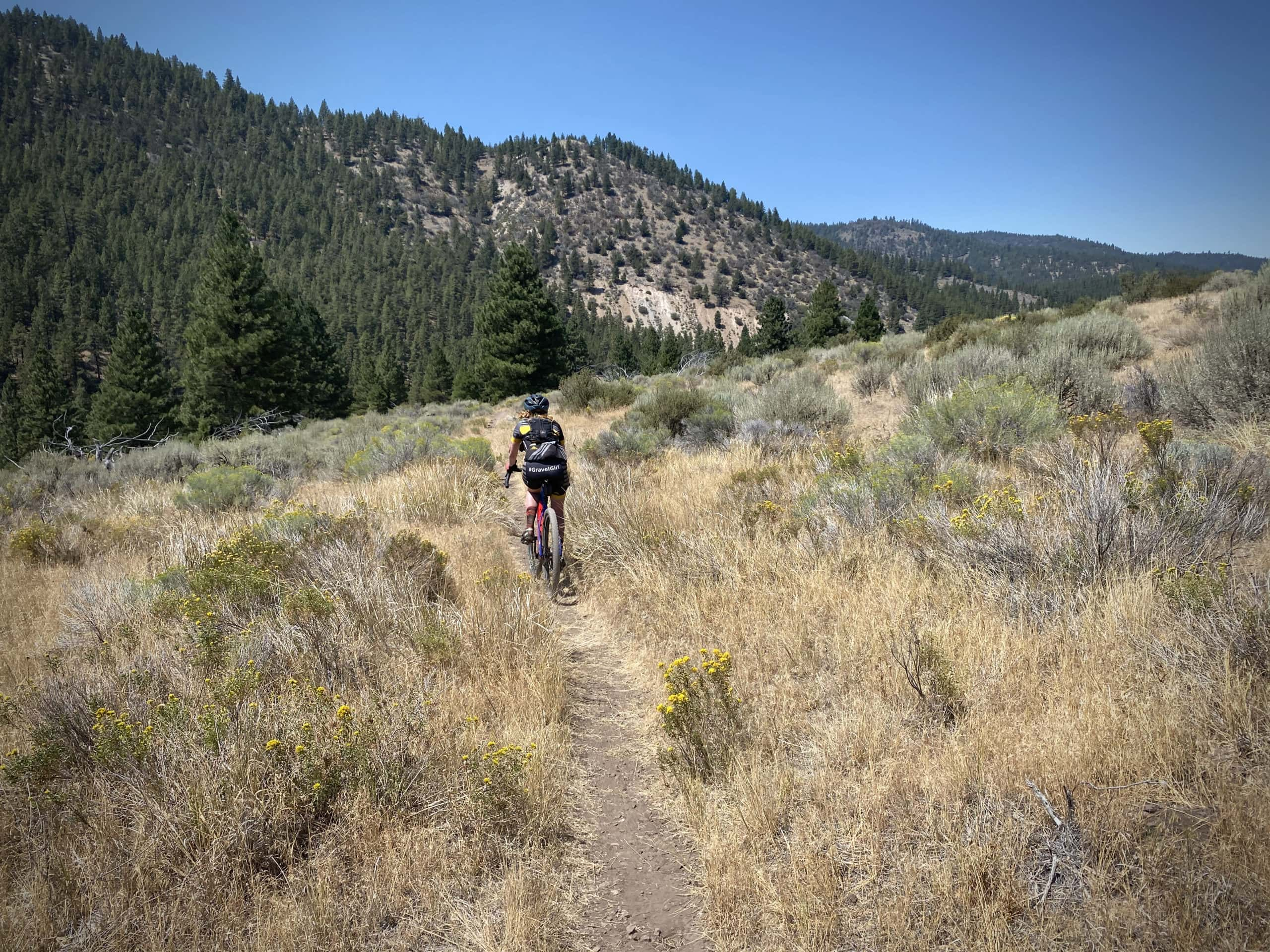 Gravel Girl riding single track in the open, rolling, grassy plains south of Paisley, Oregon.