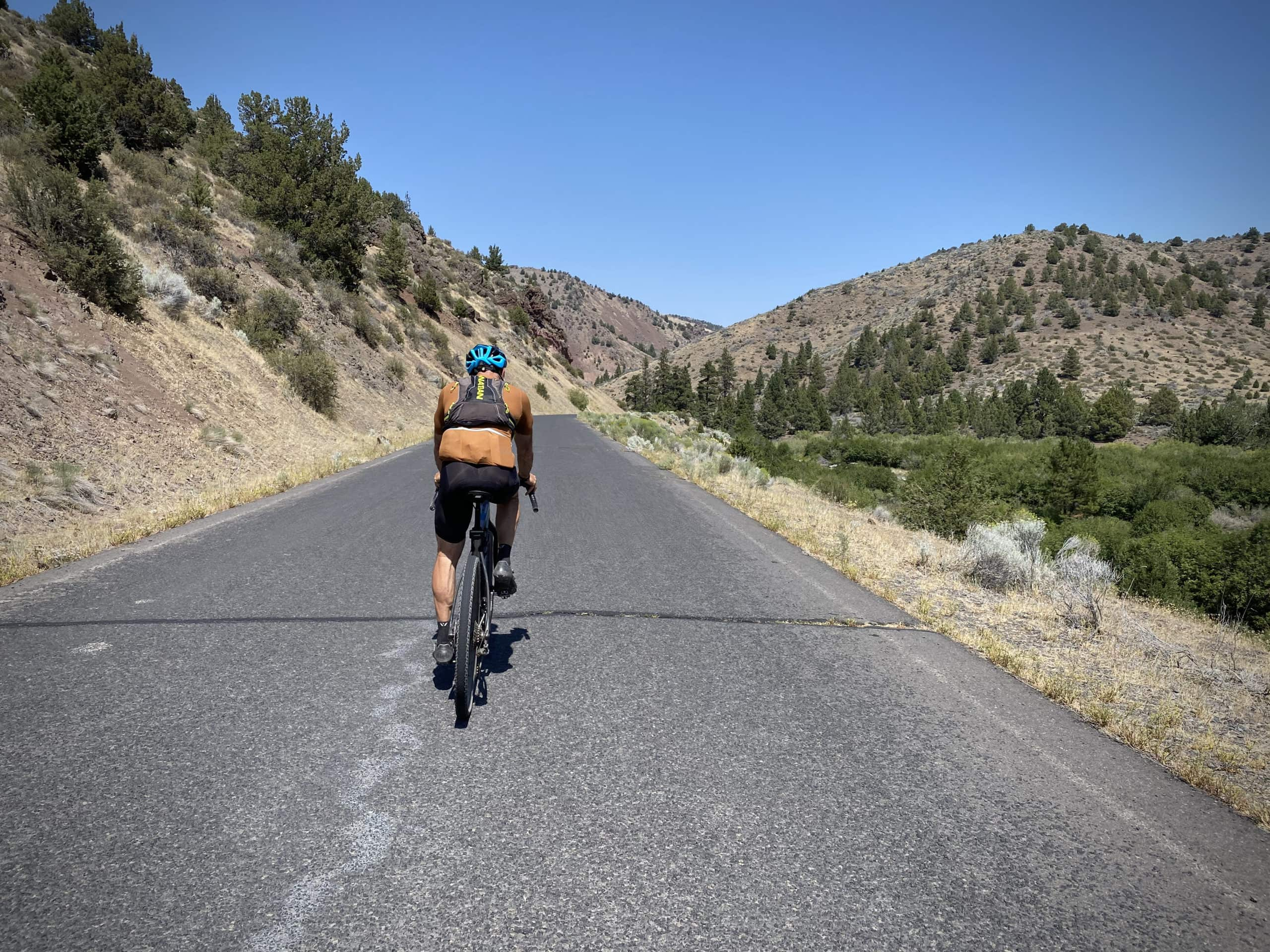 Cyclist on NF 33 riding alongside the Chewaucan River towards Paisley, Oregon.