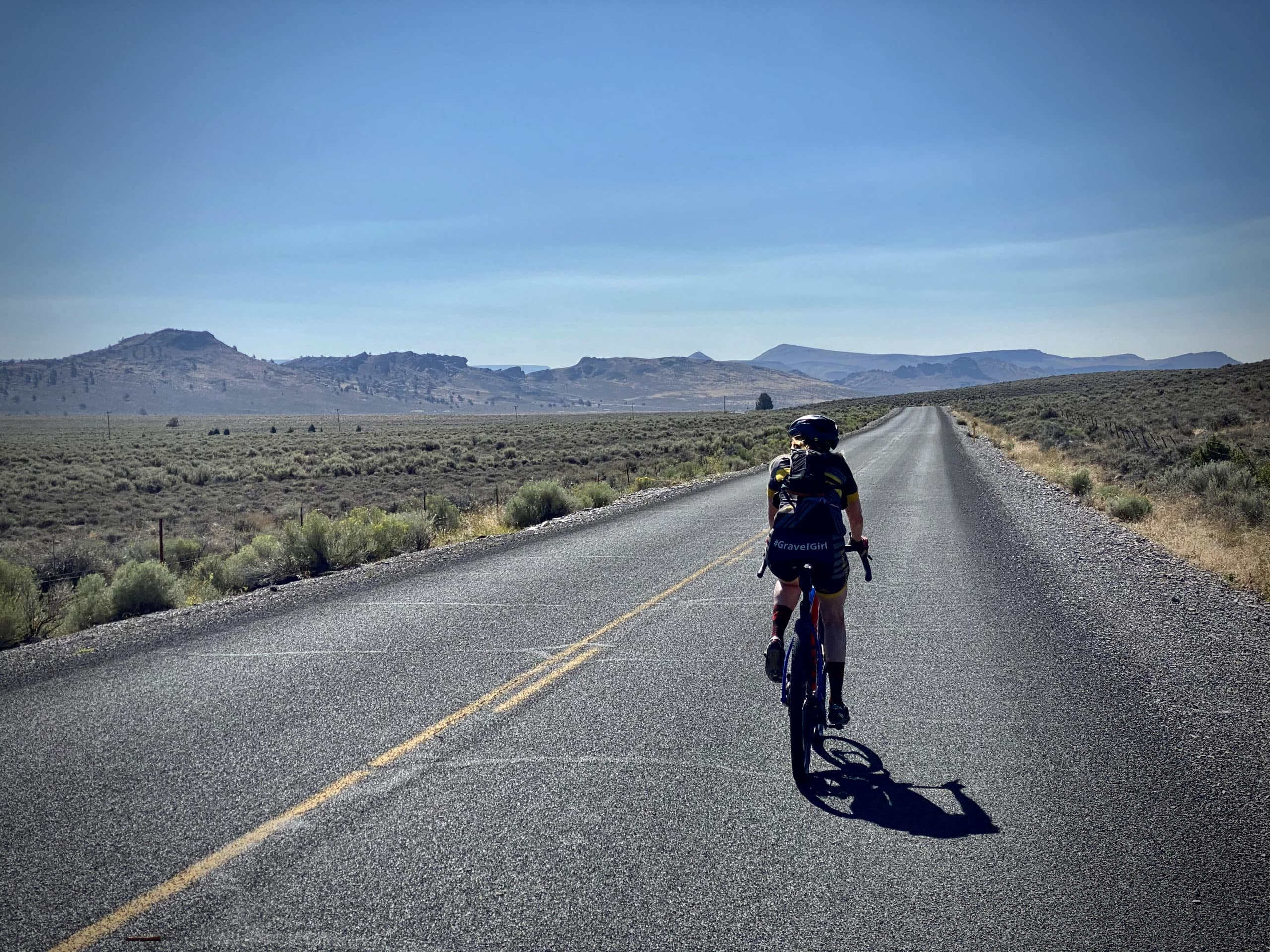 Cyclist riding south on Clover Flat road south of Paisley, Oregon.