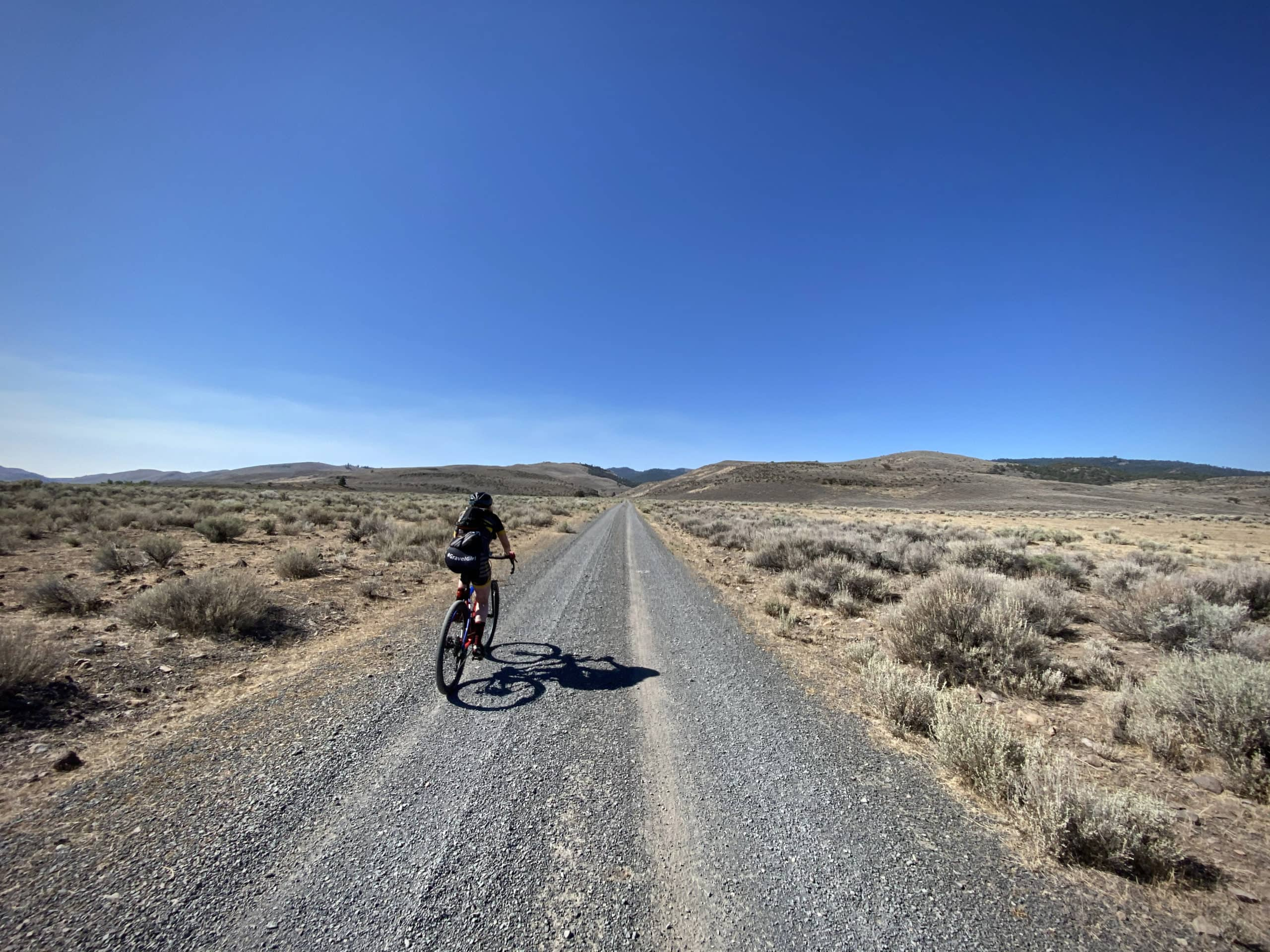 Bike rider on gravel road leading to Avery Pass and Morgan Butte in the Fremont National Forest.