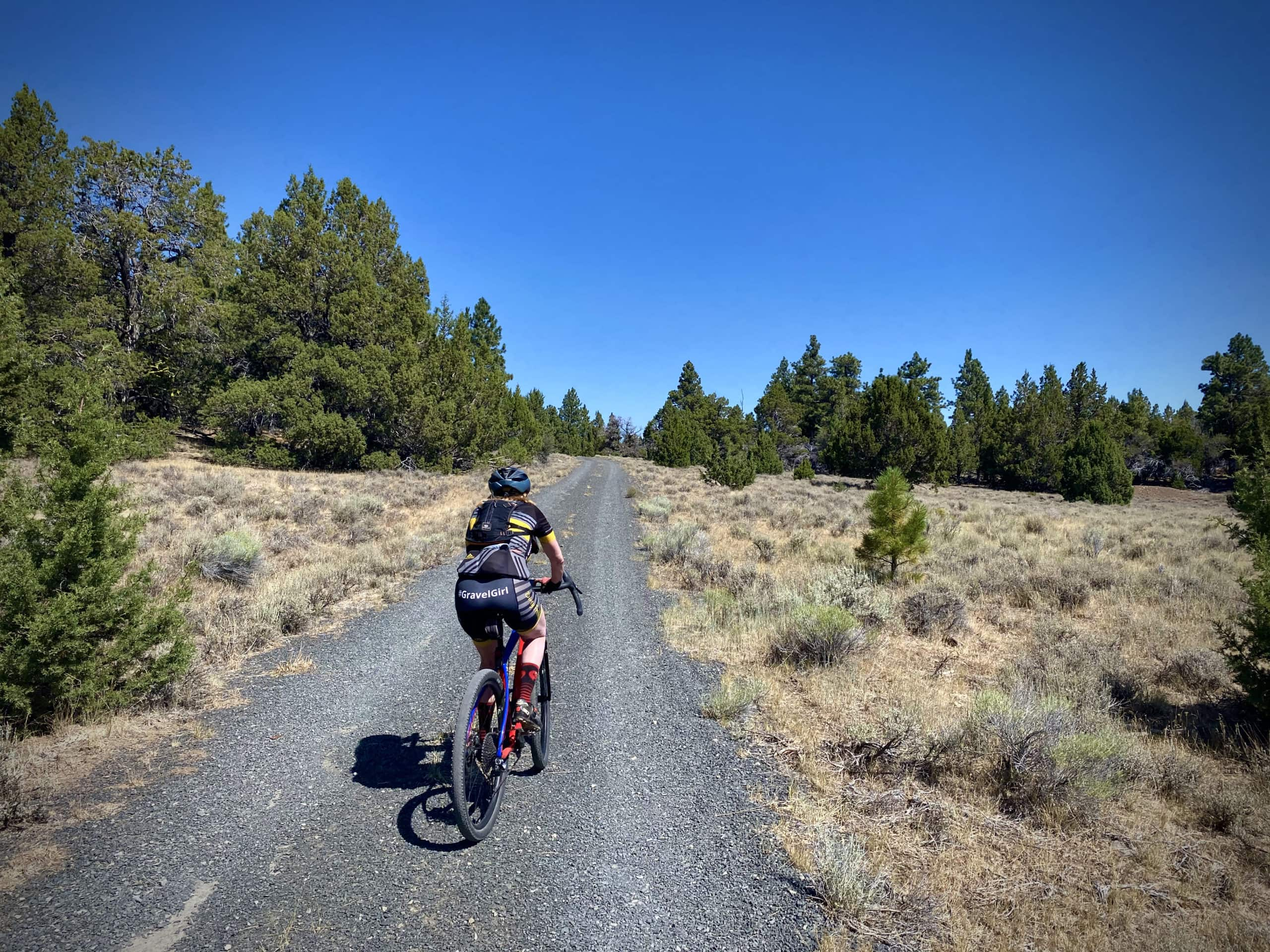 Gravel cyclist making the the turn towards Avery Pass on gravel road near Paisley, Oregon.