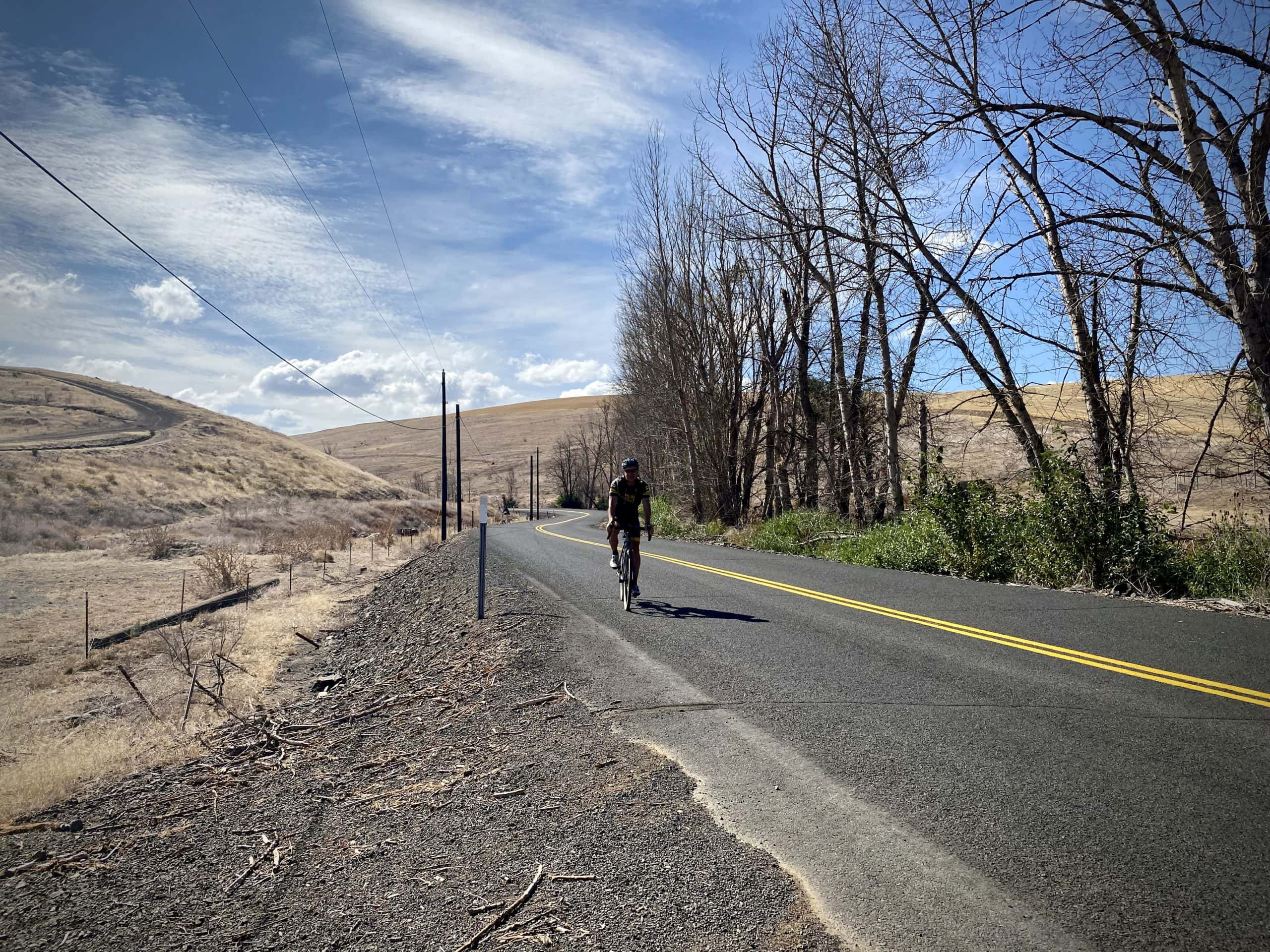 Cyclist on paved road near The Dalles, Oregon.
