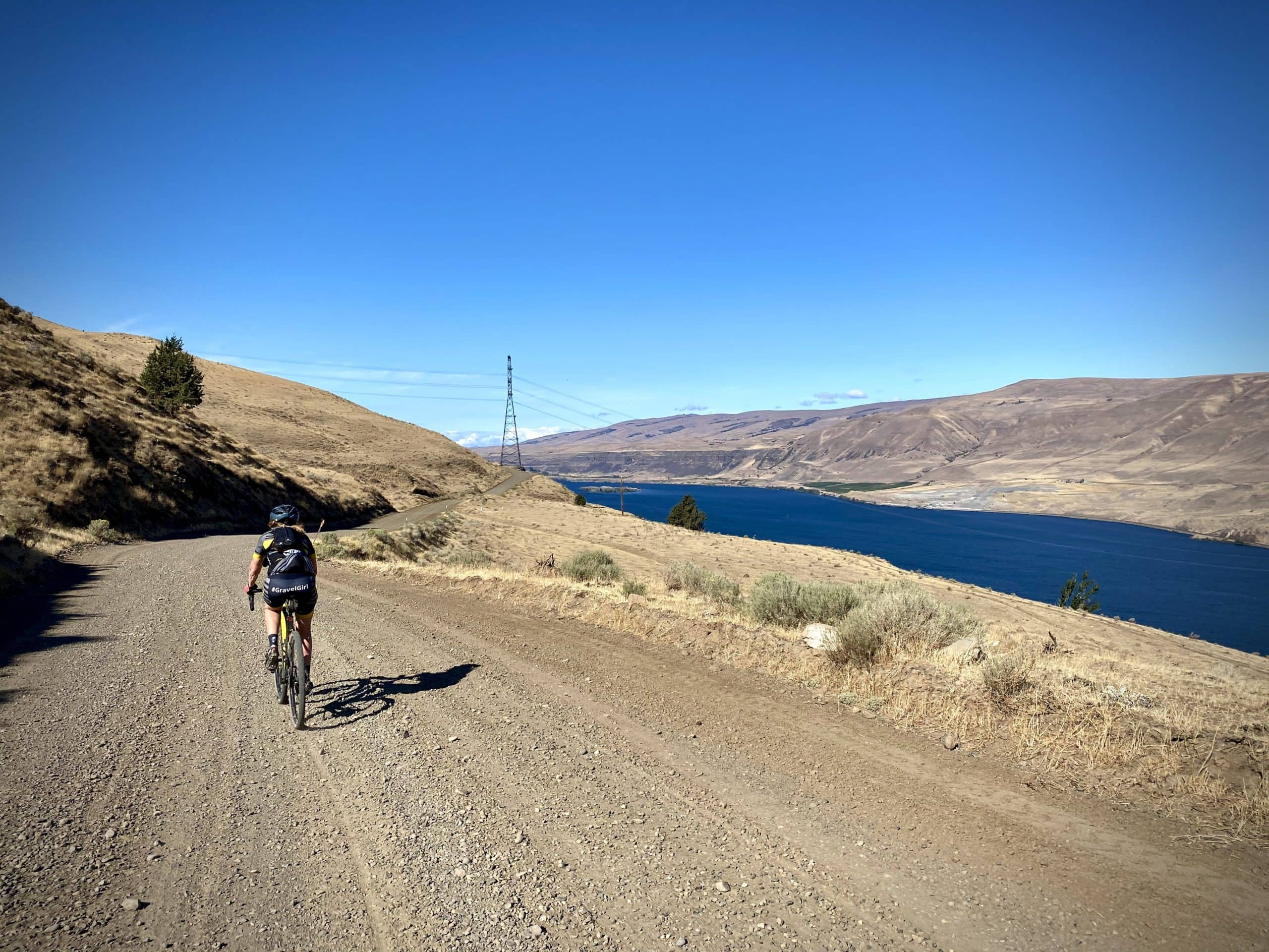 Woman gravel cyclist on Old Moody Road high above the Columbia River in Oregon.