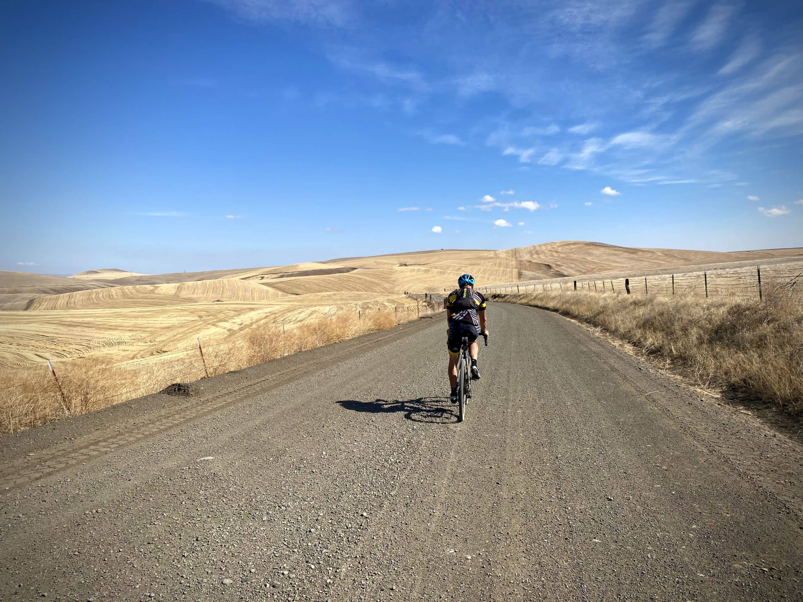 Gravel cyclist on wide open gravel road in the Tygh Valley area.