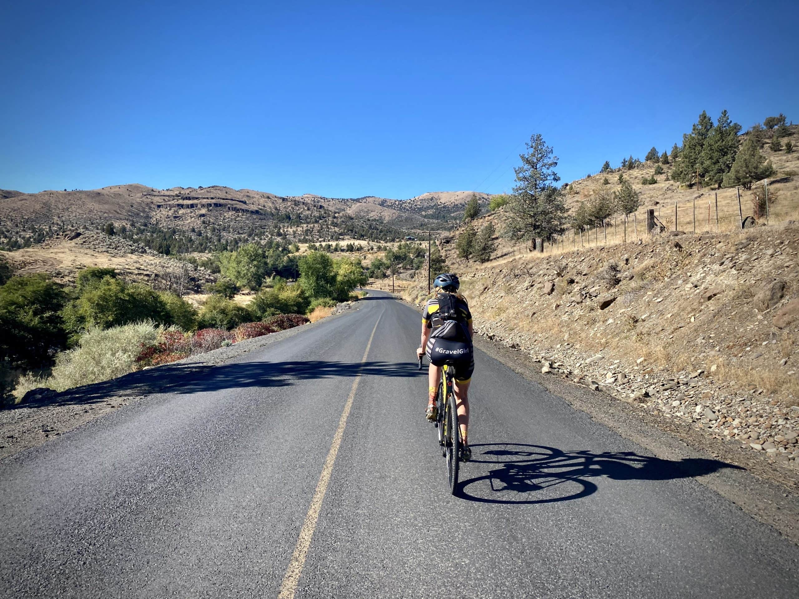 Gravel Girl leading out on paved road along the South Fork of the John Day river in Oregon.