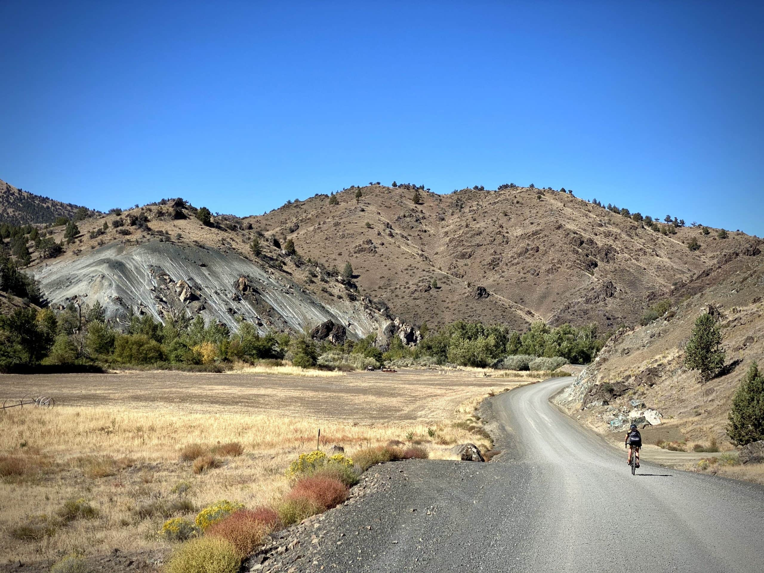 Gravel cyclist nearing the town of Dayville with colorful hills in the background.