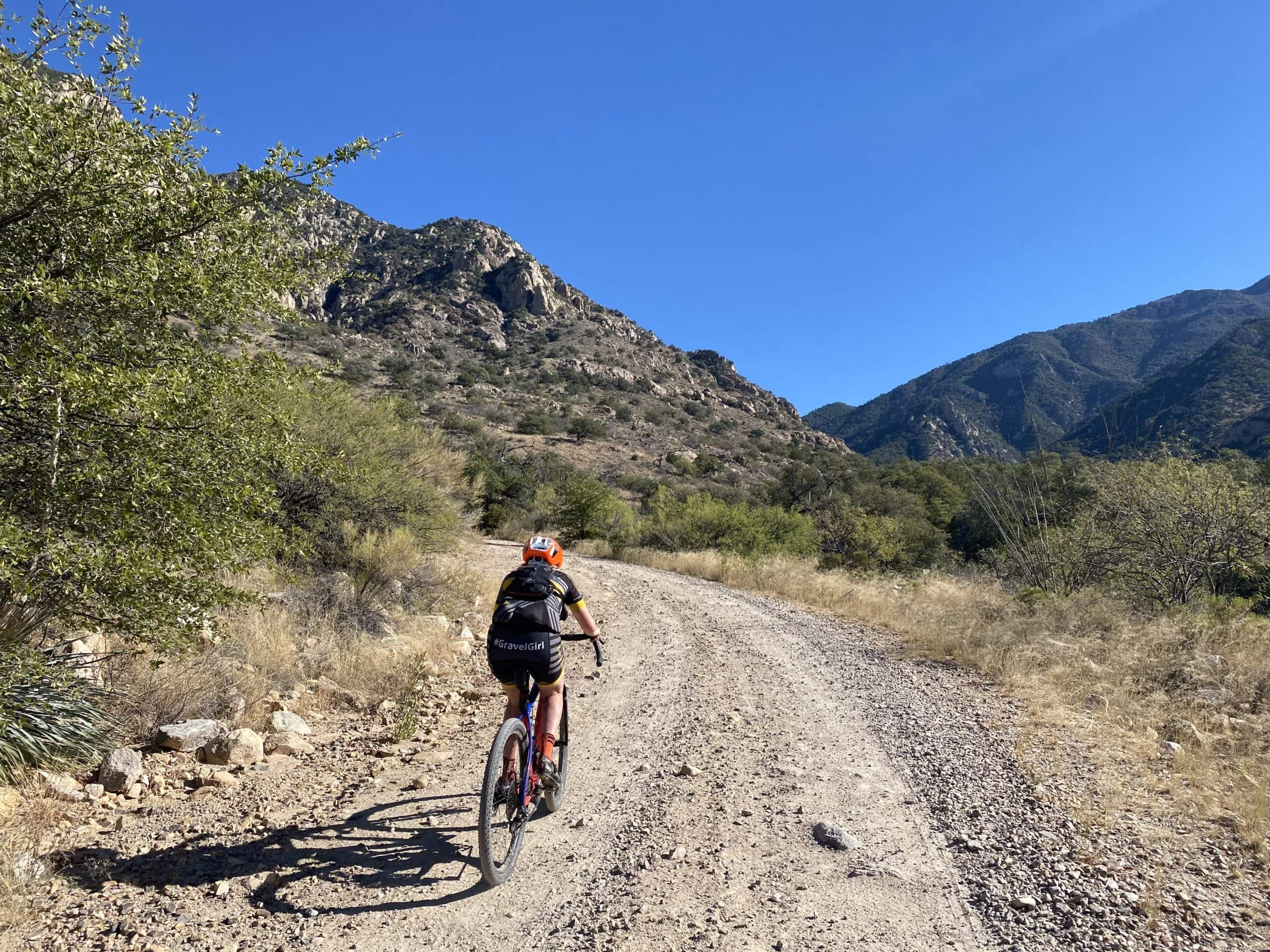 Cyclist on gravel road with Santa Rita mountains in the background.