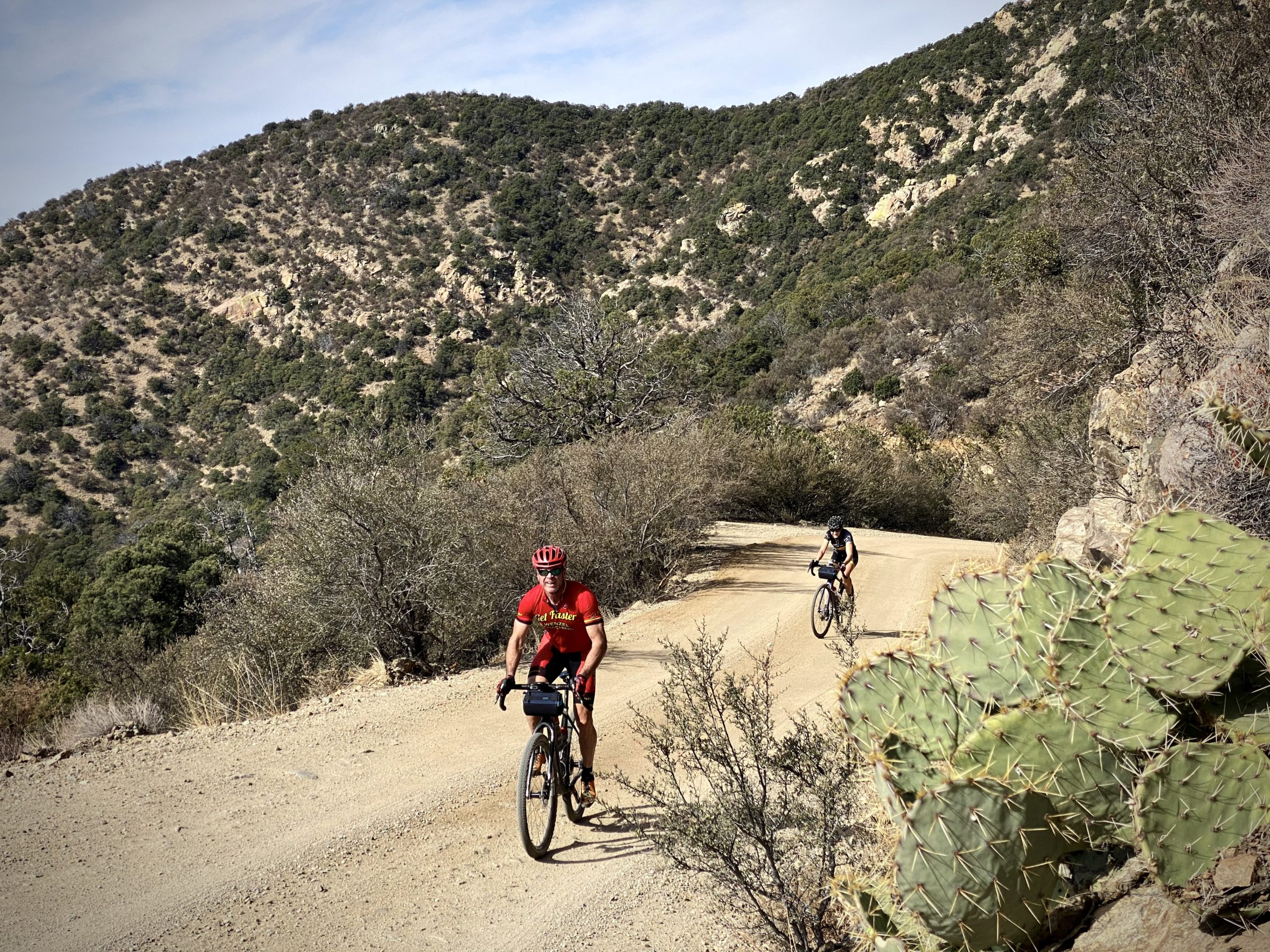 Two cyclists climbing up the gravel portion of Mt Hopkins road near Tucson, Arizona.
