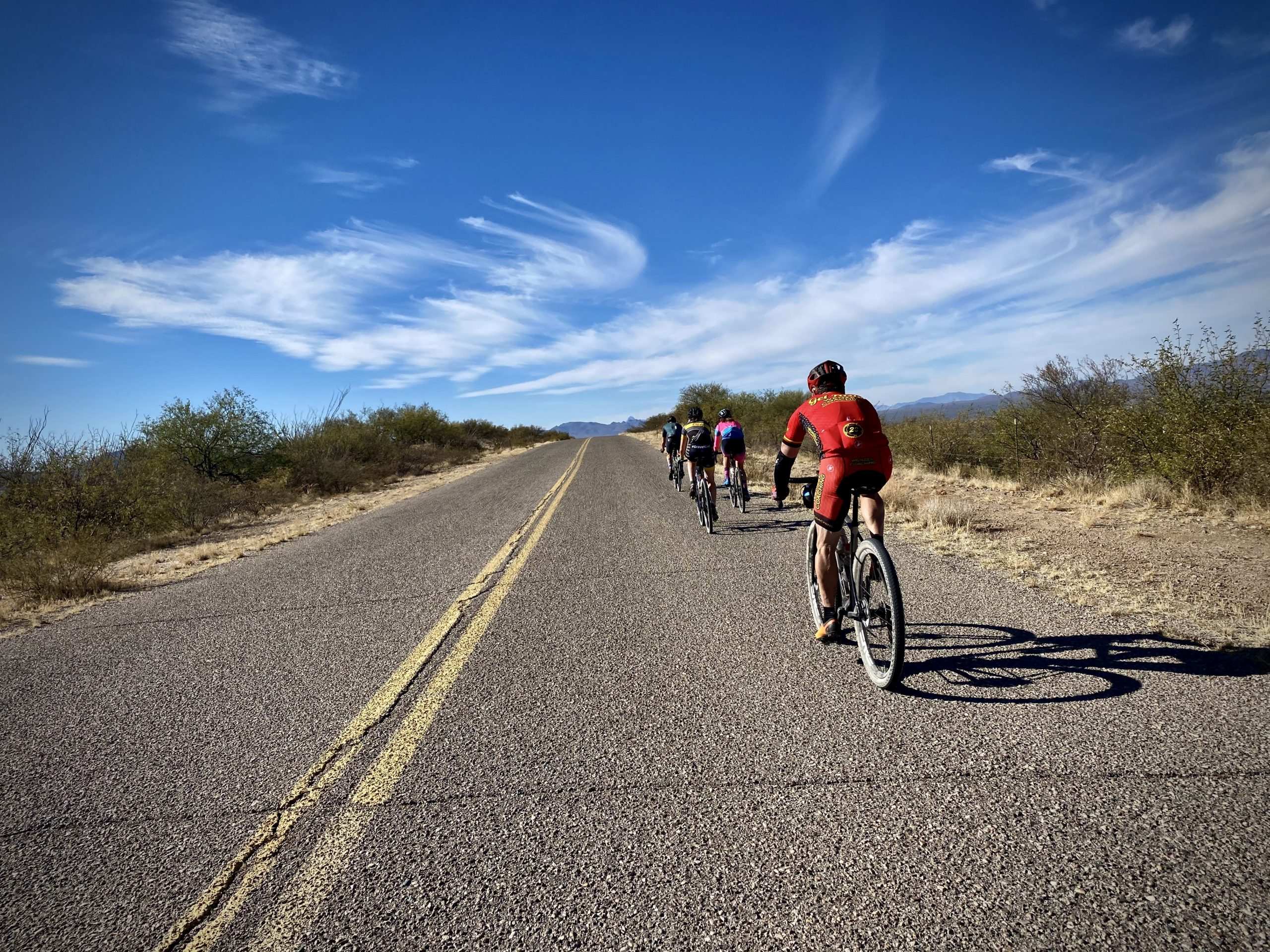 A group of cyclists riding single file downhill near the Whipple Observatory Visitors Center.