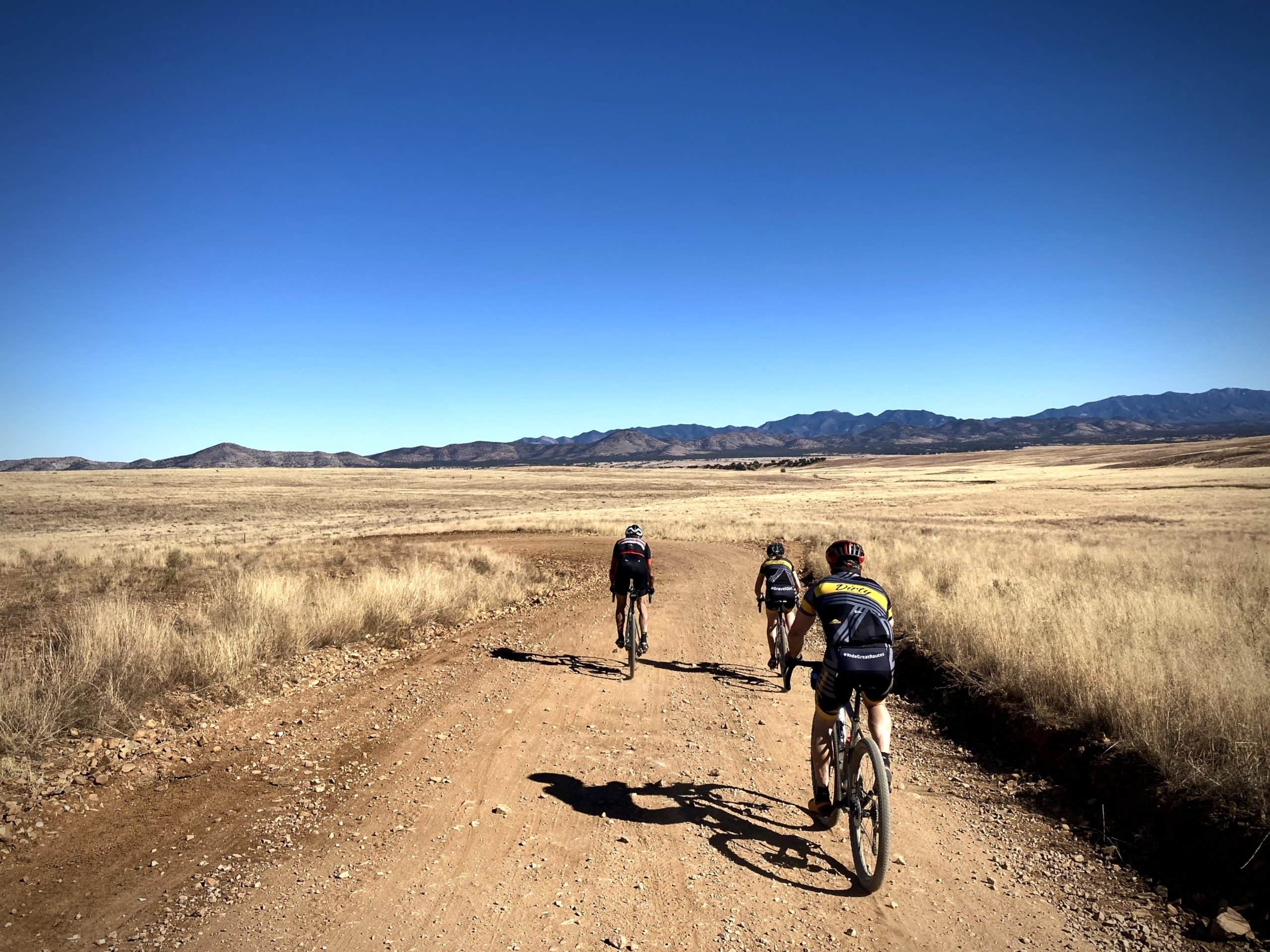 Group of cyclists riding in the San Rafael Valley with golden grasses in the background.