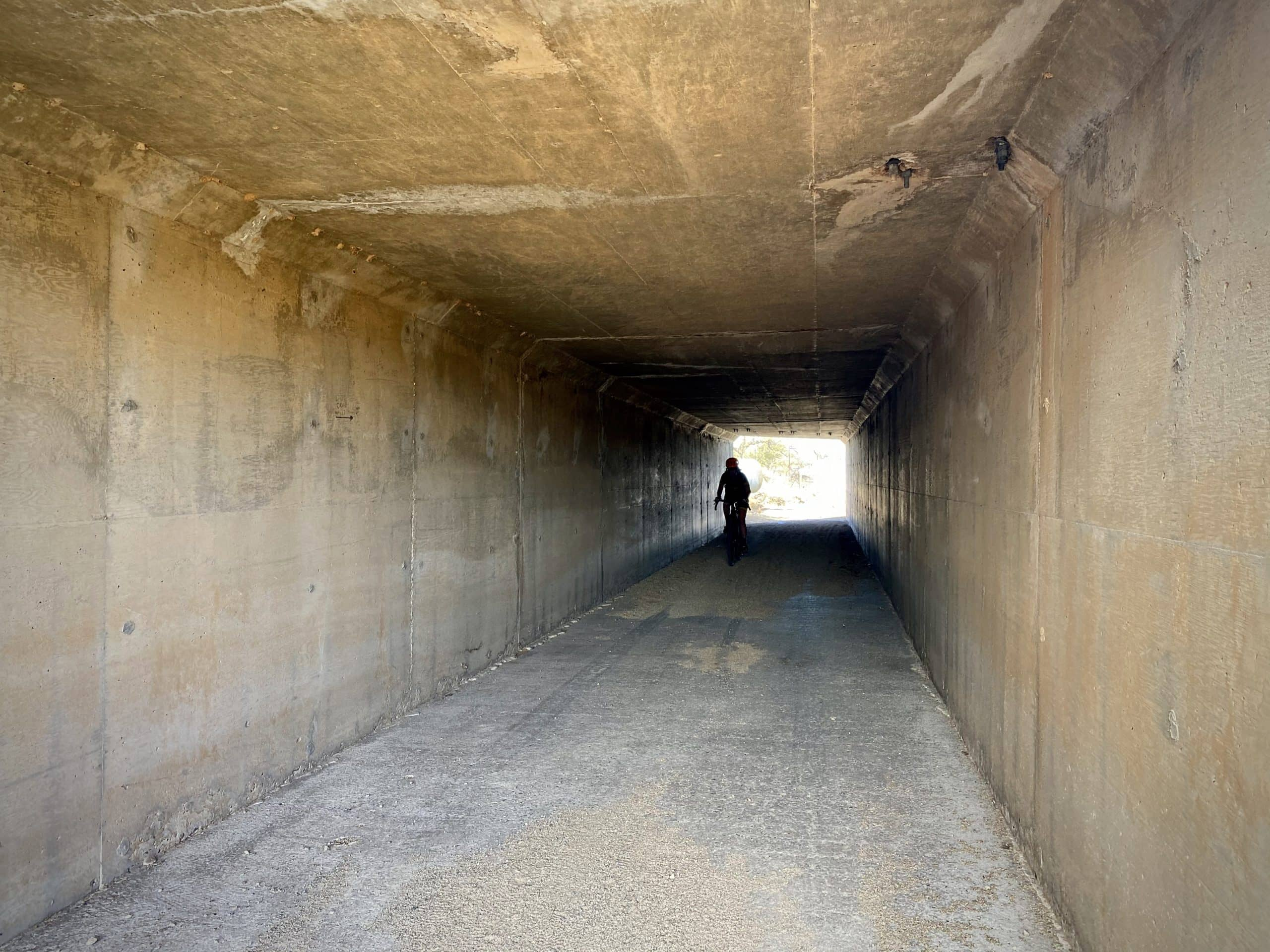 Cyclist passing through tunnel underneath the Sonoita Highway on the AZT.
