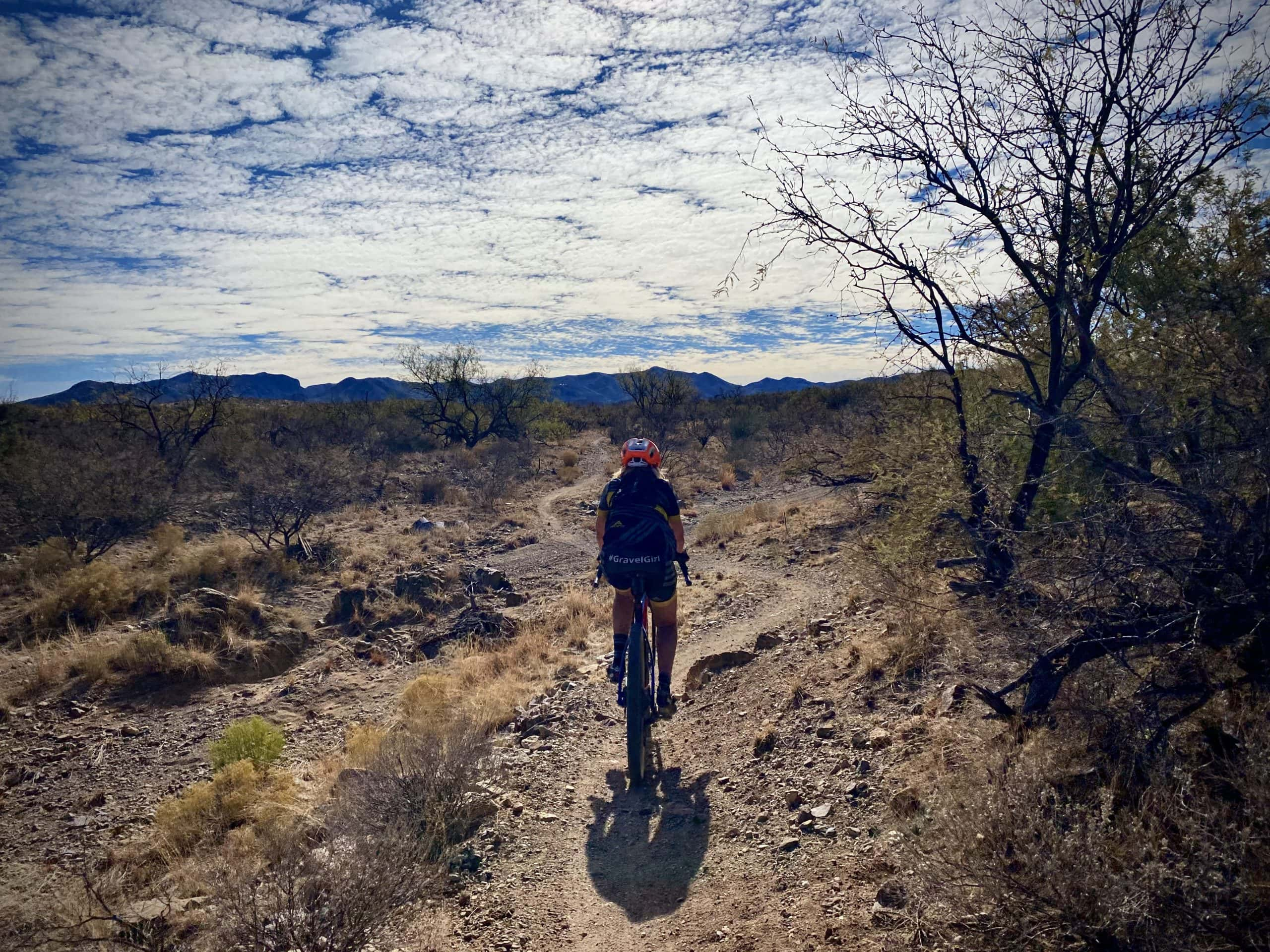 Woman gravel cyclist on downward section of AZT.