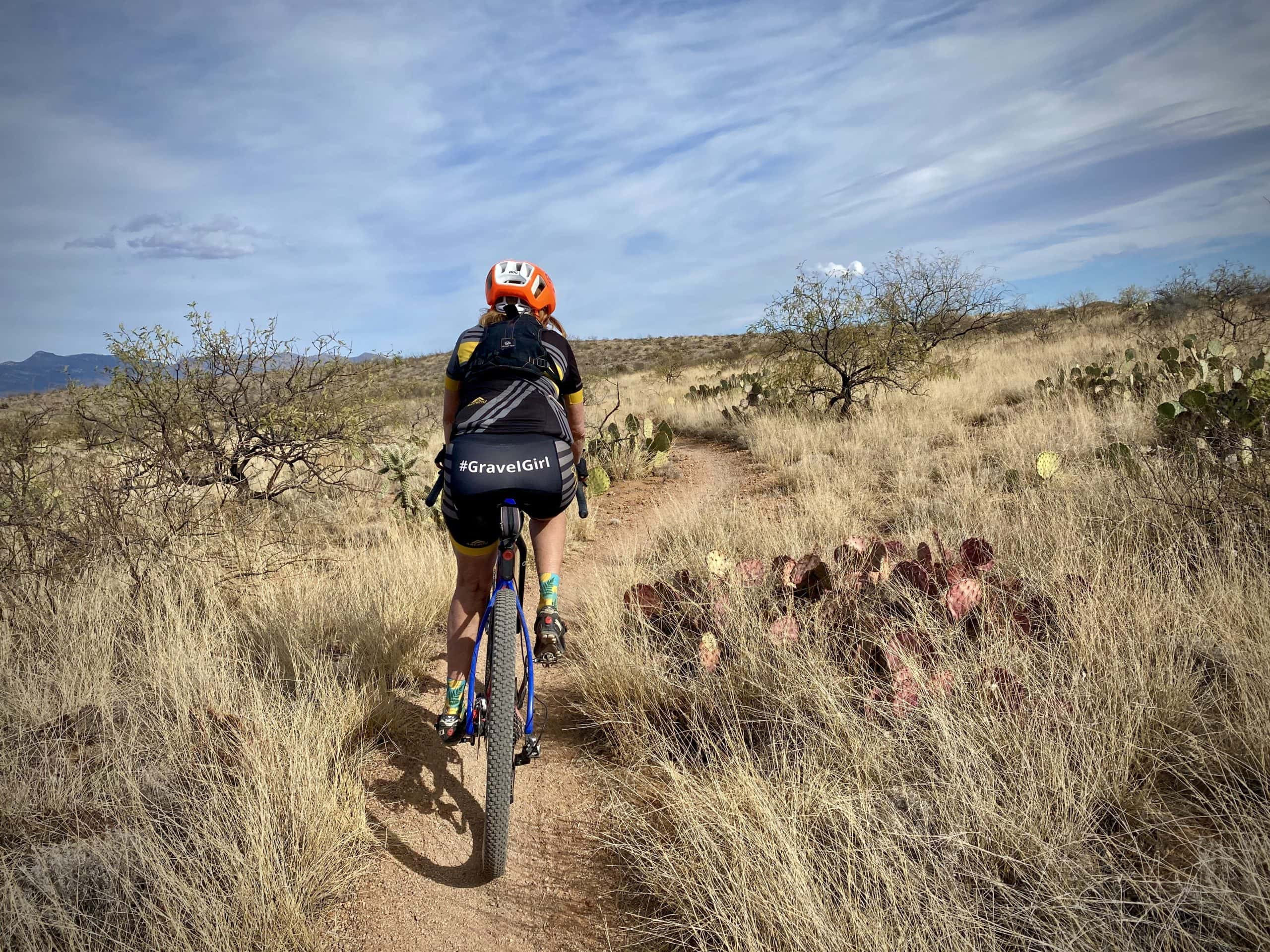 Woman cyclist riding section of AZT with tall grasses.