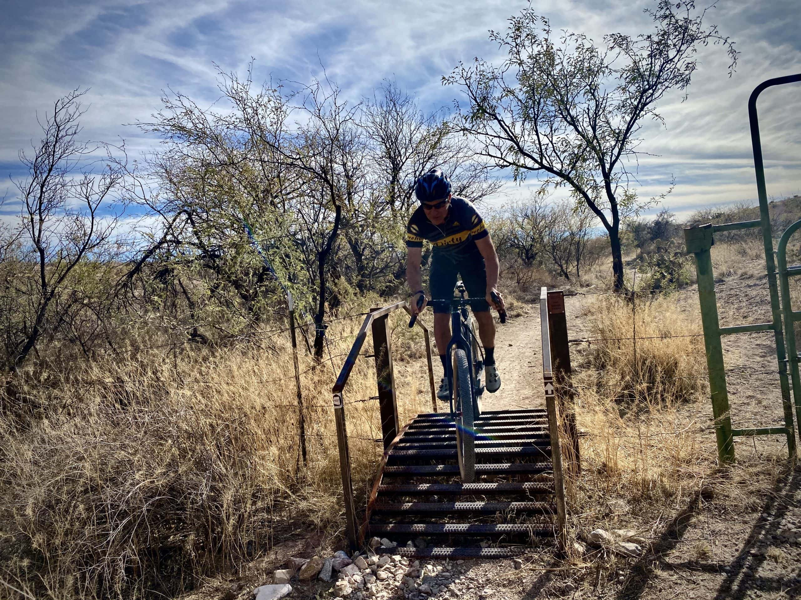 Cyclist passing through cattle fence using an up and over bicycle ladder on the AZT.