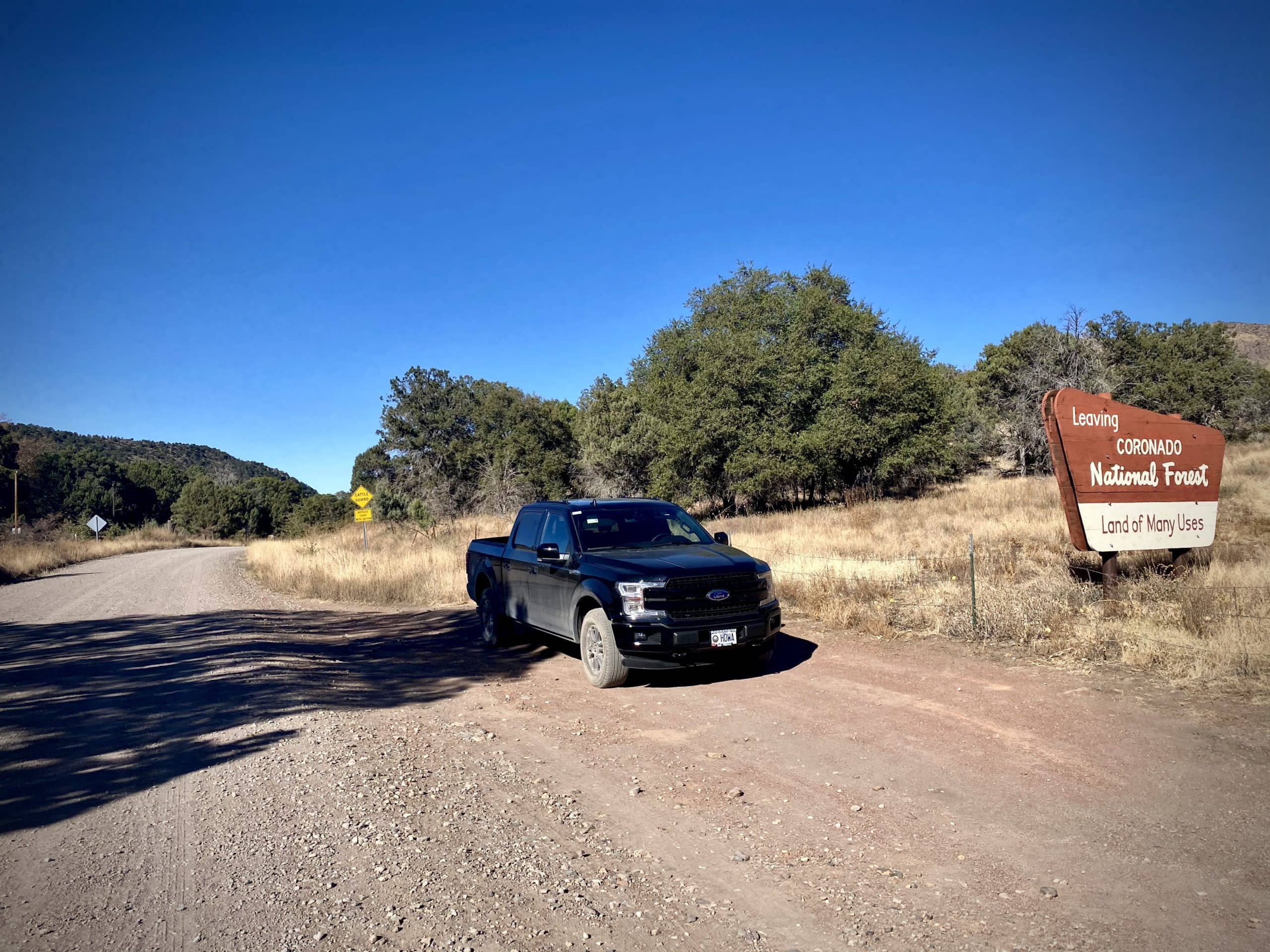 Ford F150 truck parked on dirt road at sign for Coronado National Forest in the Chiricahua Mountains.
