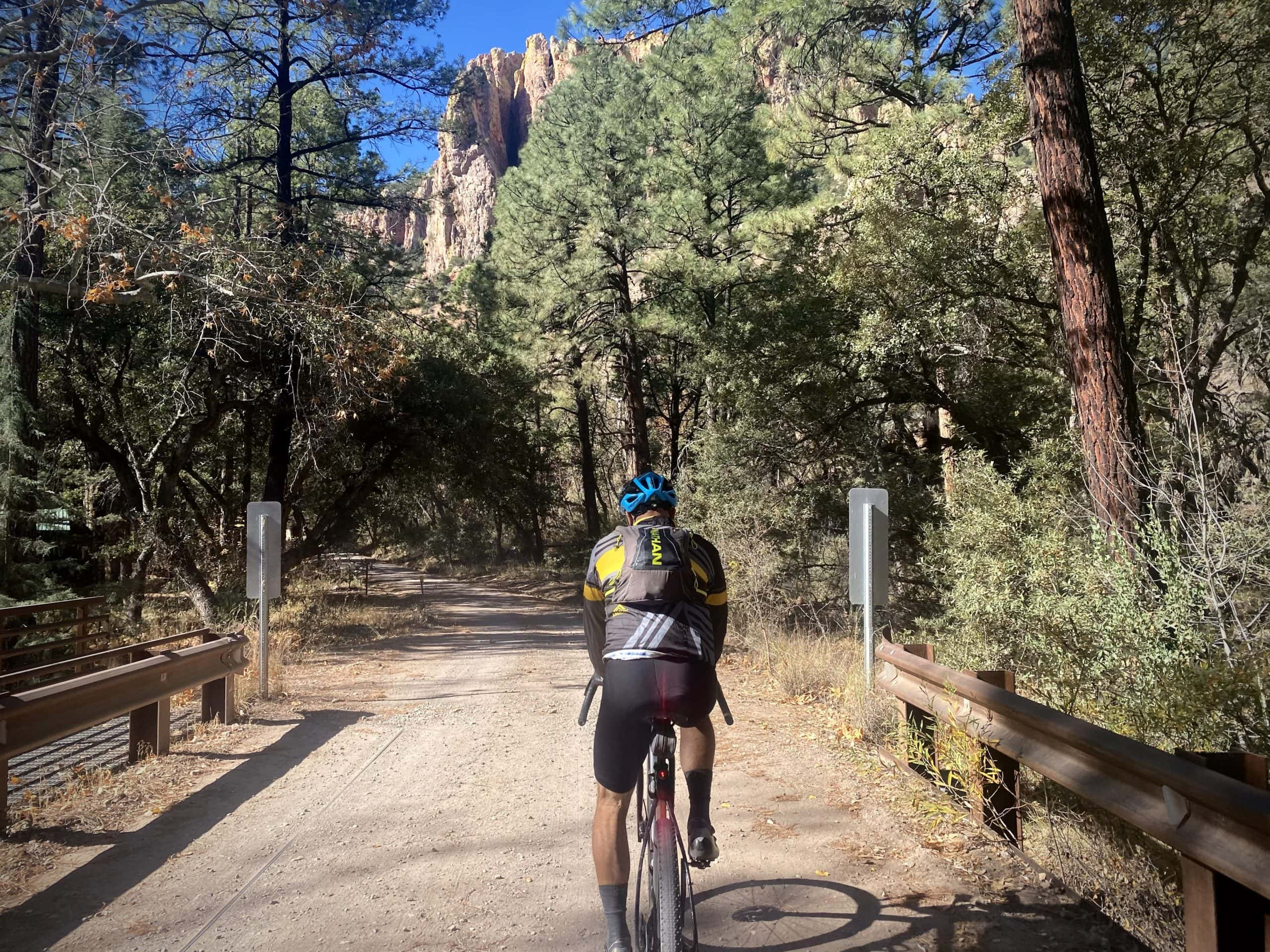 Cyclist crossing Cave Creek differentiating the paved road from the gravel road,