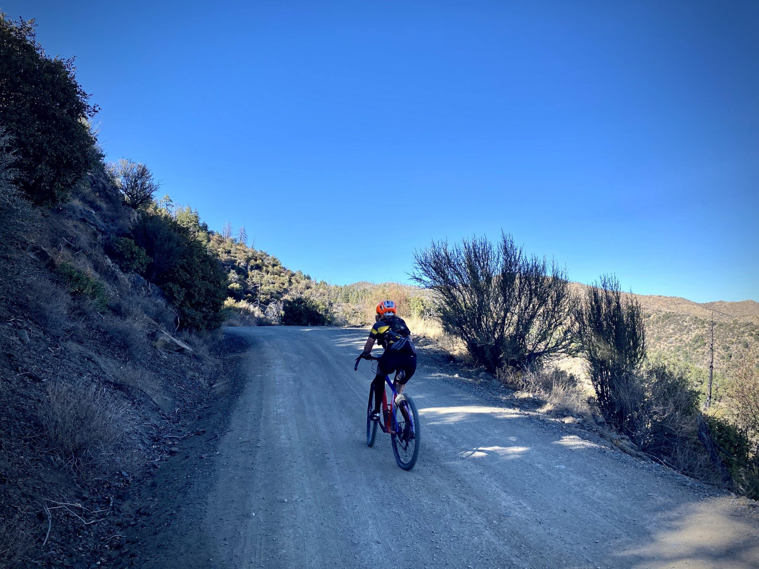 Cyclist in the shadows high on ridge of dirt road in Chiricahua Mountains.