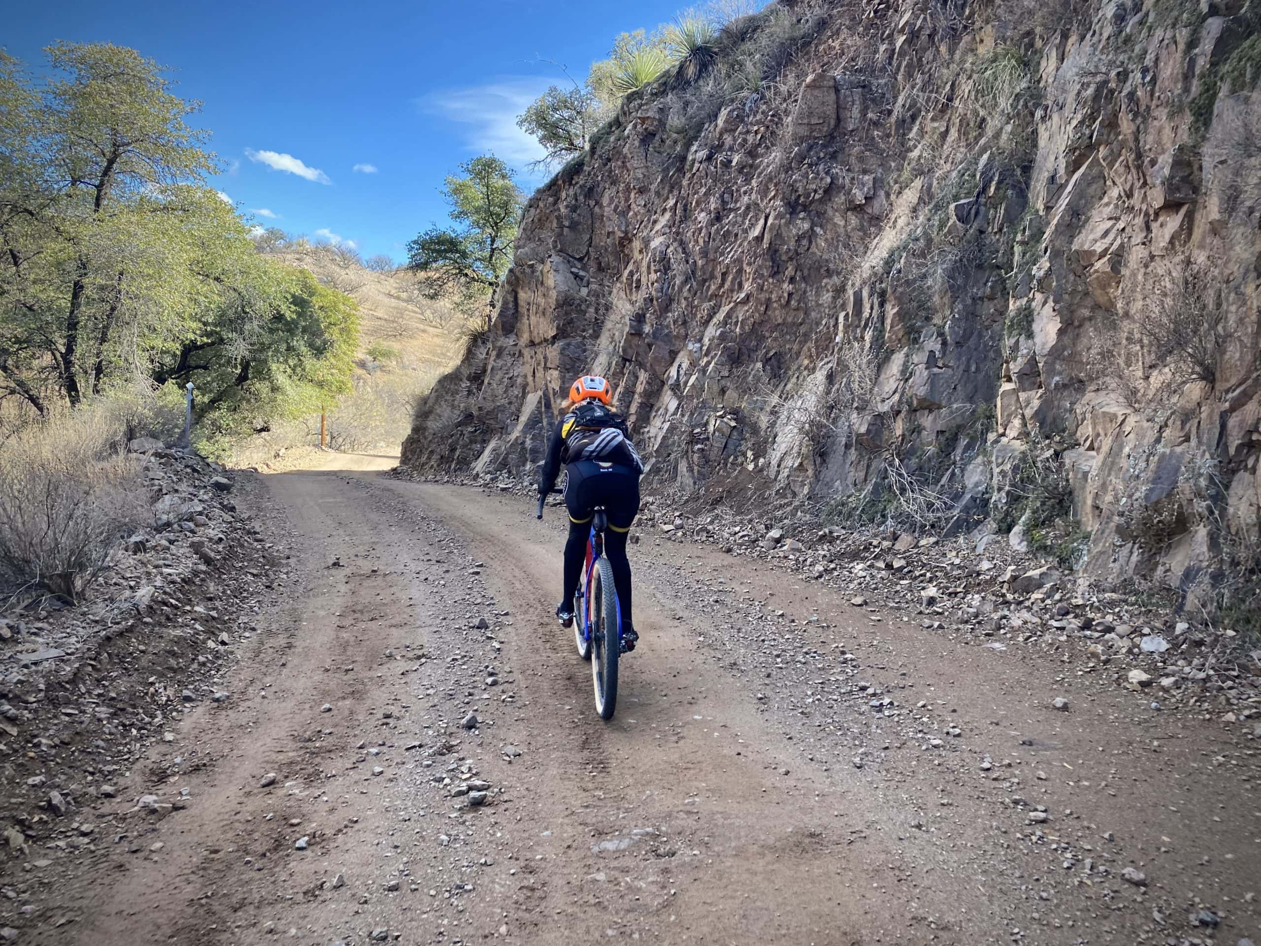 Bike rider on gravel road with rock, cliff wall to the right near Patagonia, AZ.