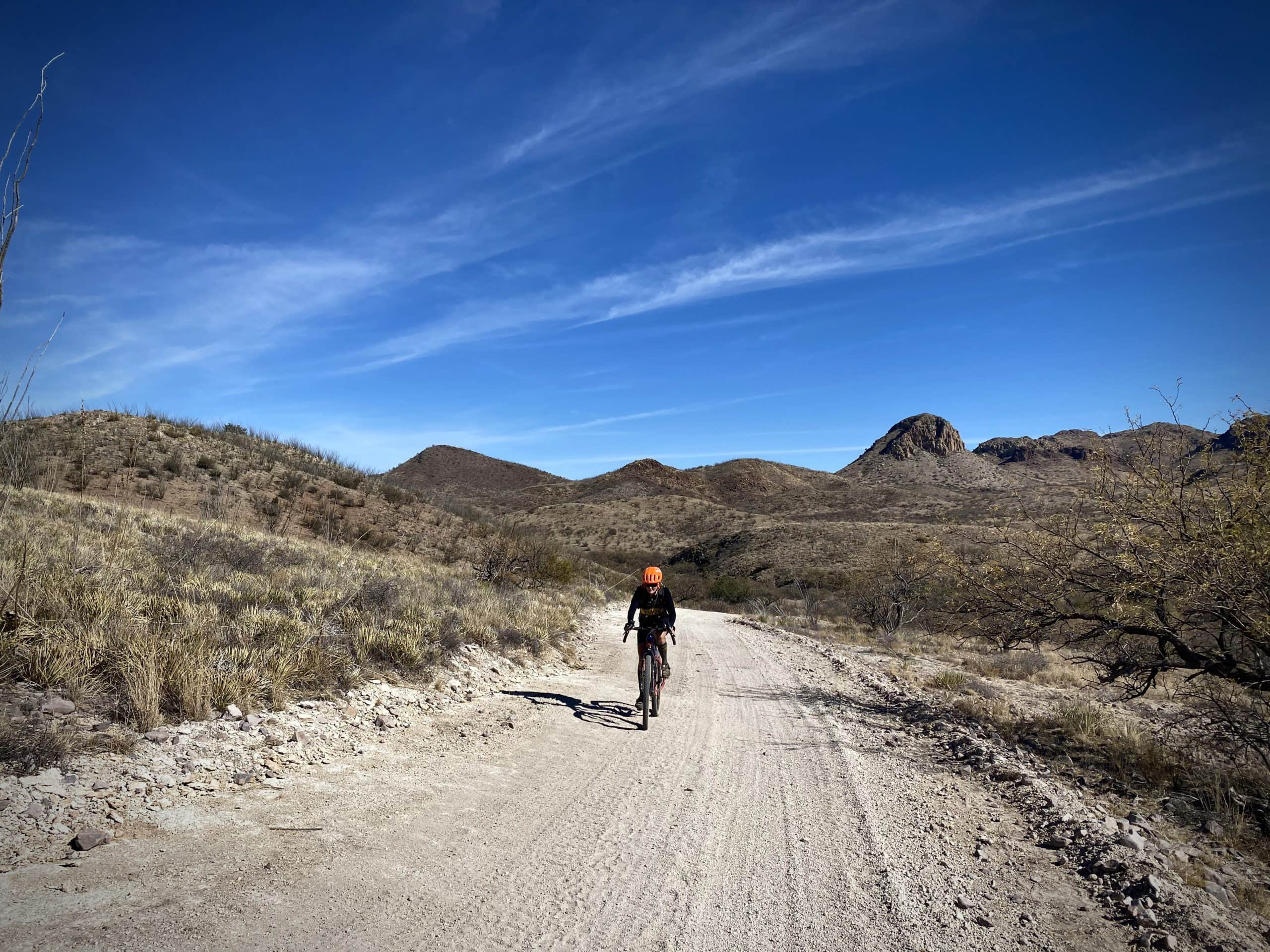 Woman cyclist riding white gravel road south of Tucson.