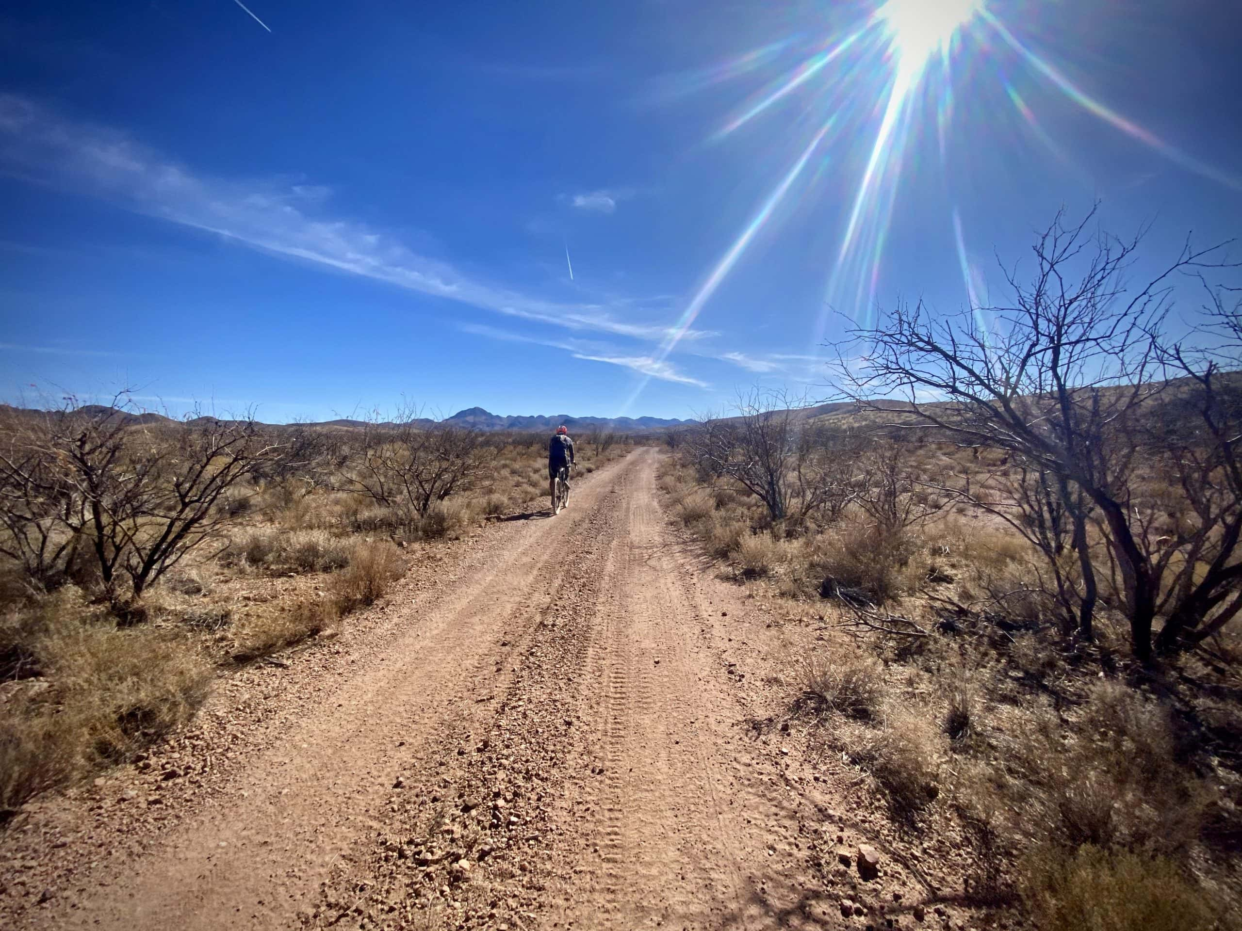 Cyclist on red dirt road that is long and straight.