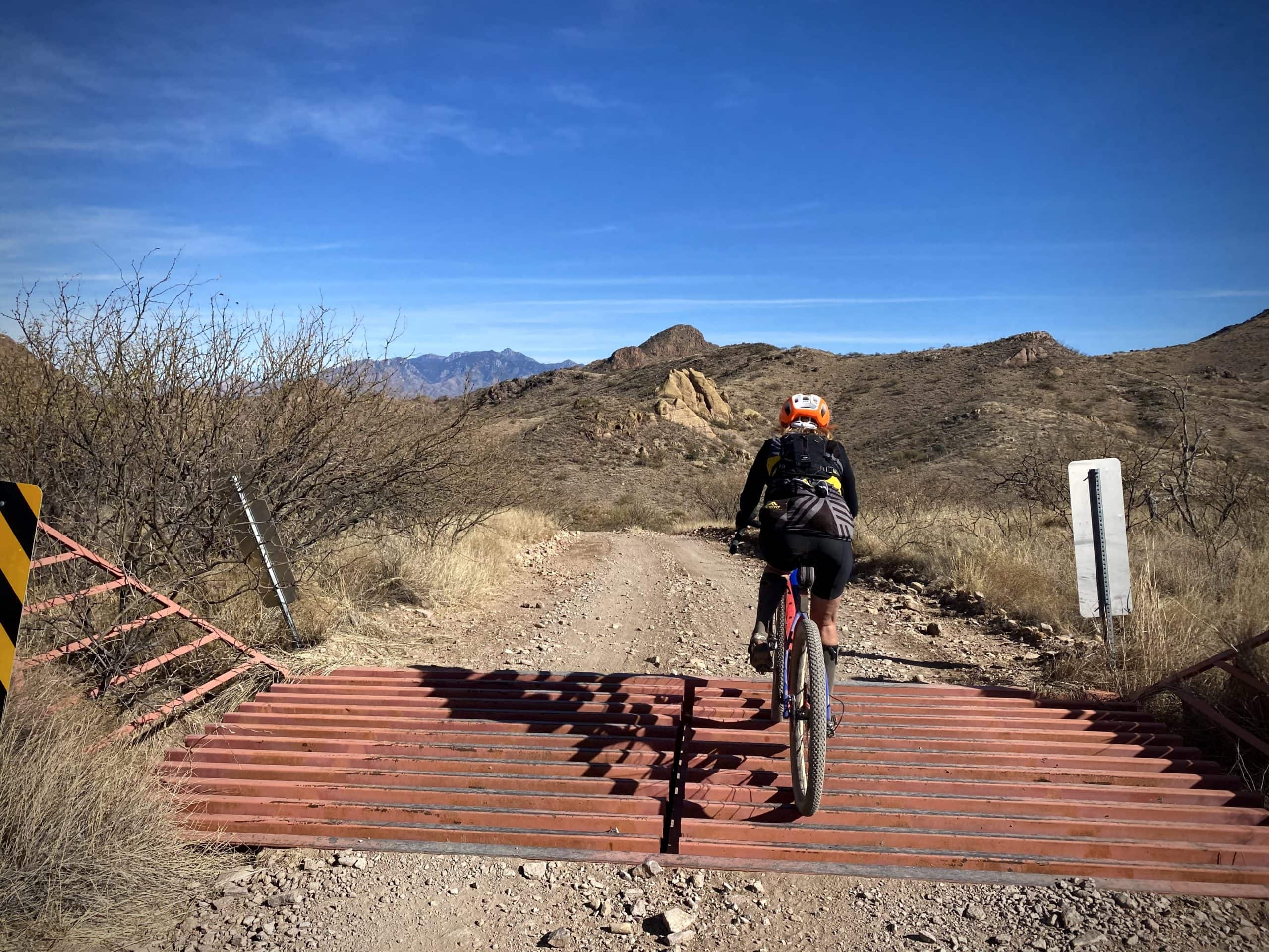 Gravel cyclist passing over cattle grate in Tumacacori Mountains south of Tucson.