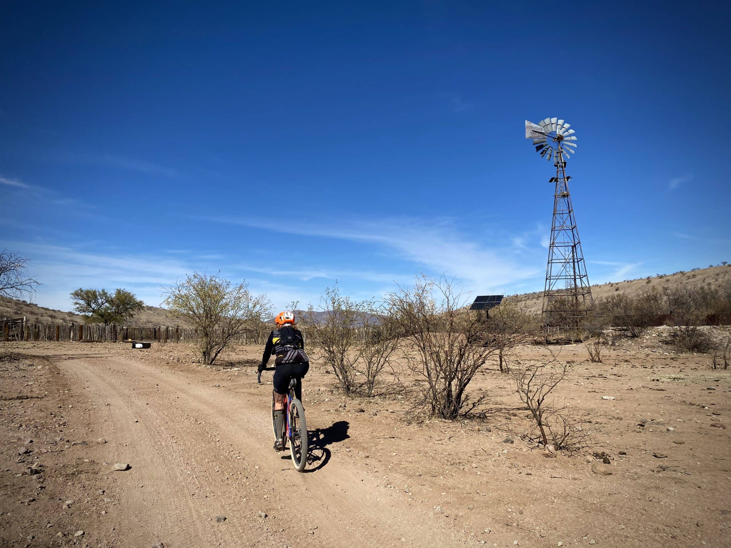 Gravel Girl riding past old windmill in Tumacacori Mountains south of Arivaca.