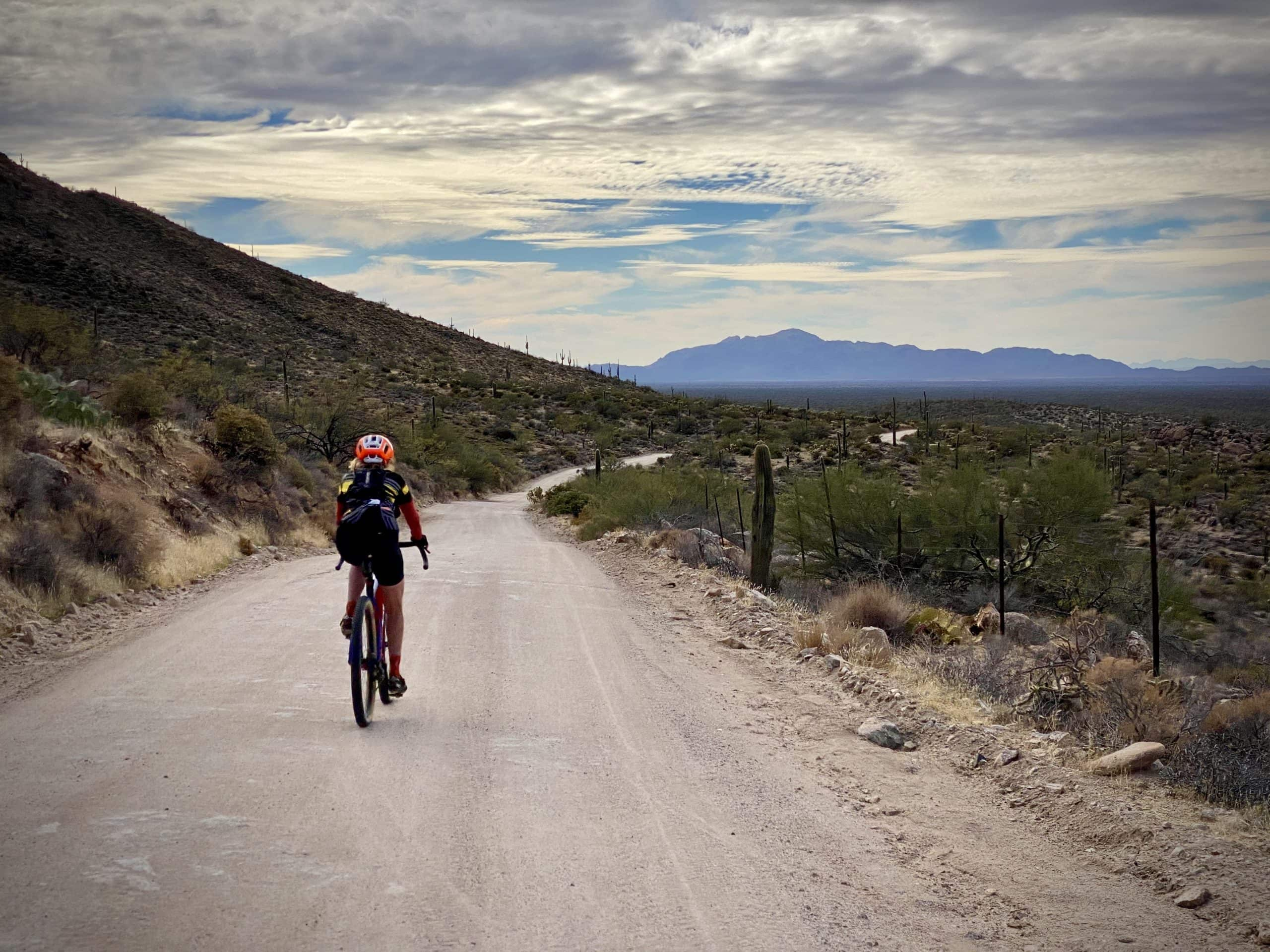Woman cyclist on the gravel of 96 Ranch Road north of Tucson, Arizona.