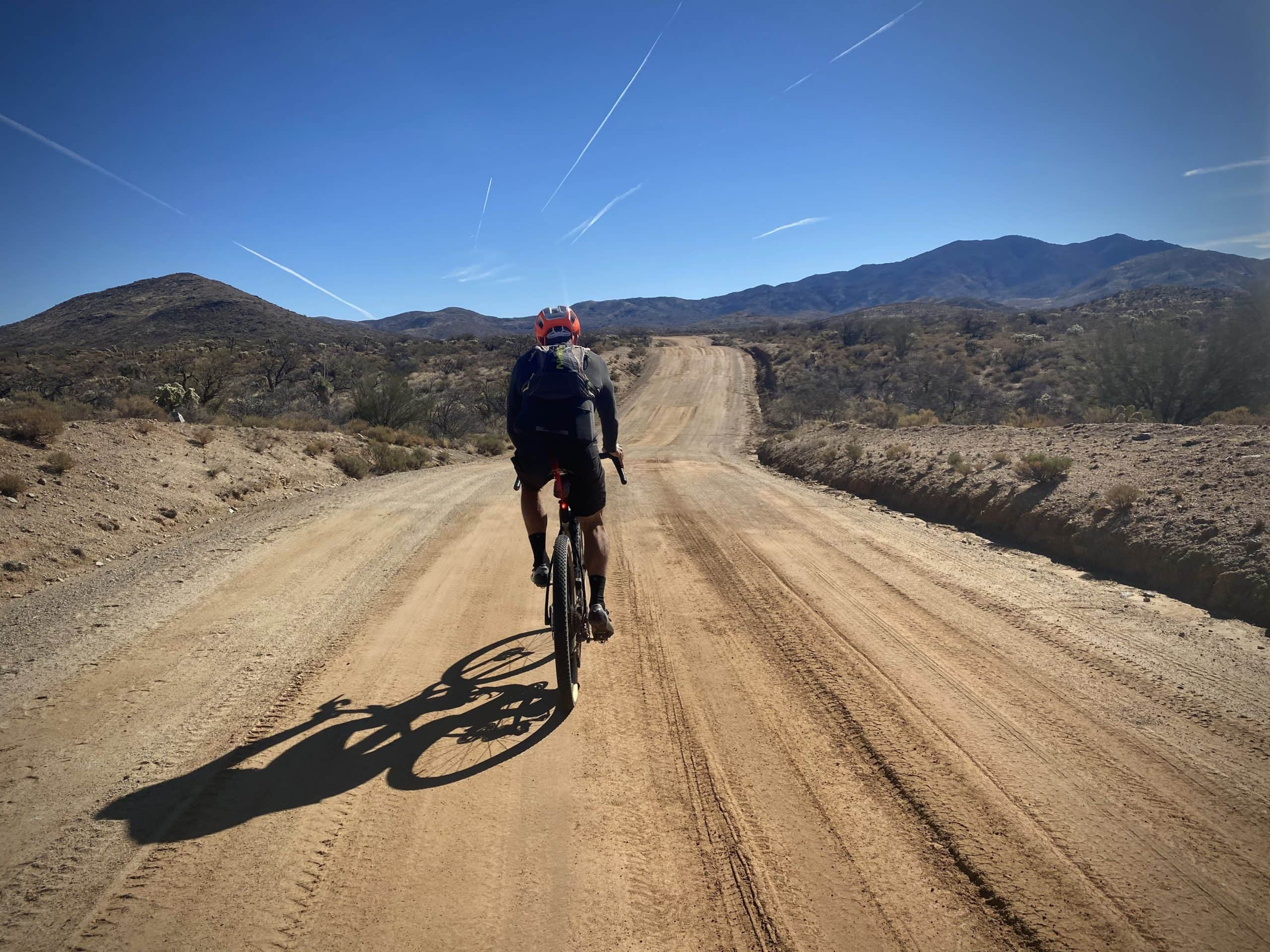 Gravel cyclist riding Freeman road with mountains in the background.