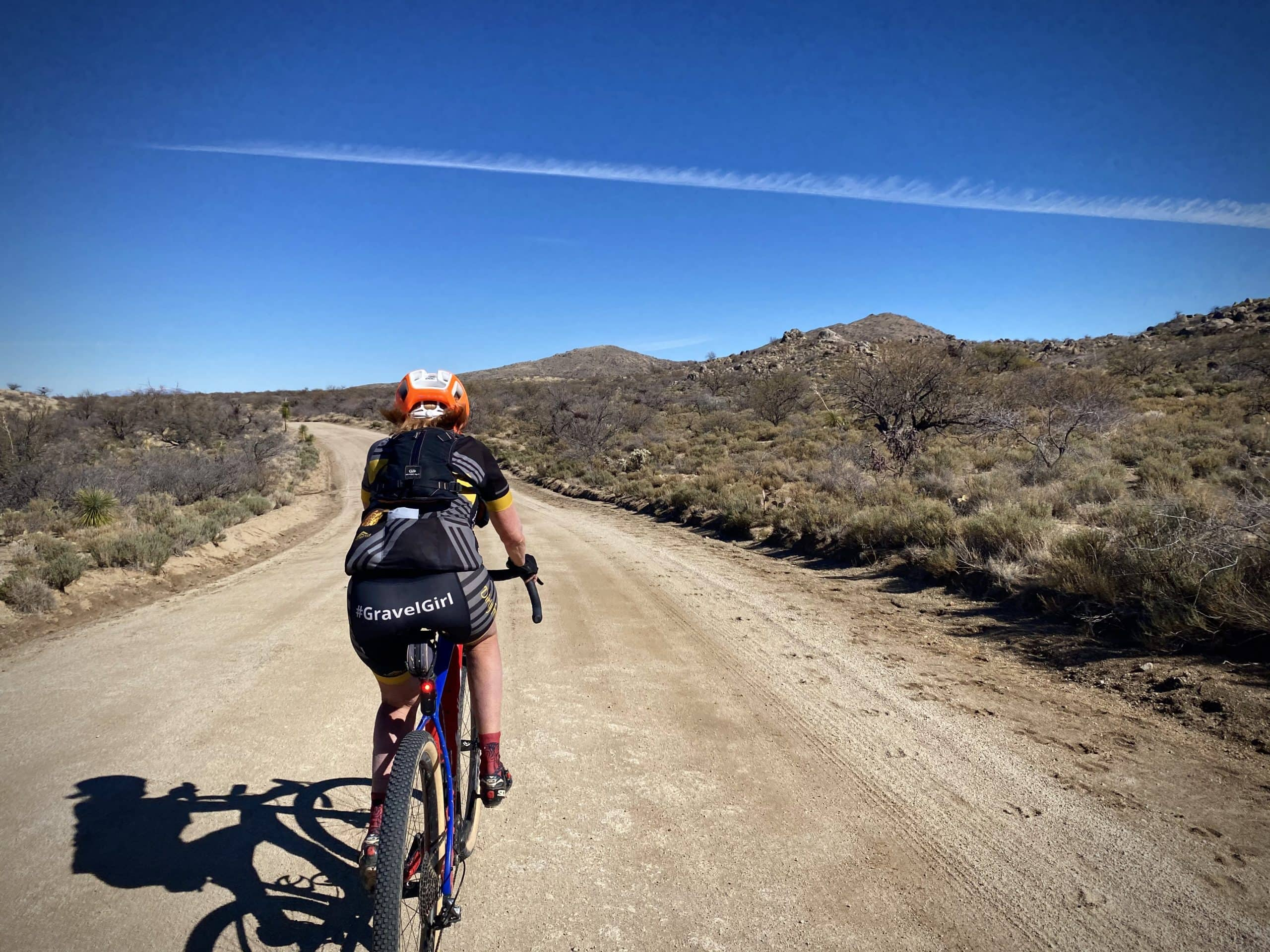 Gravel Girl on unpaved road with boulders in the background.