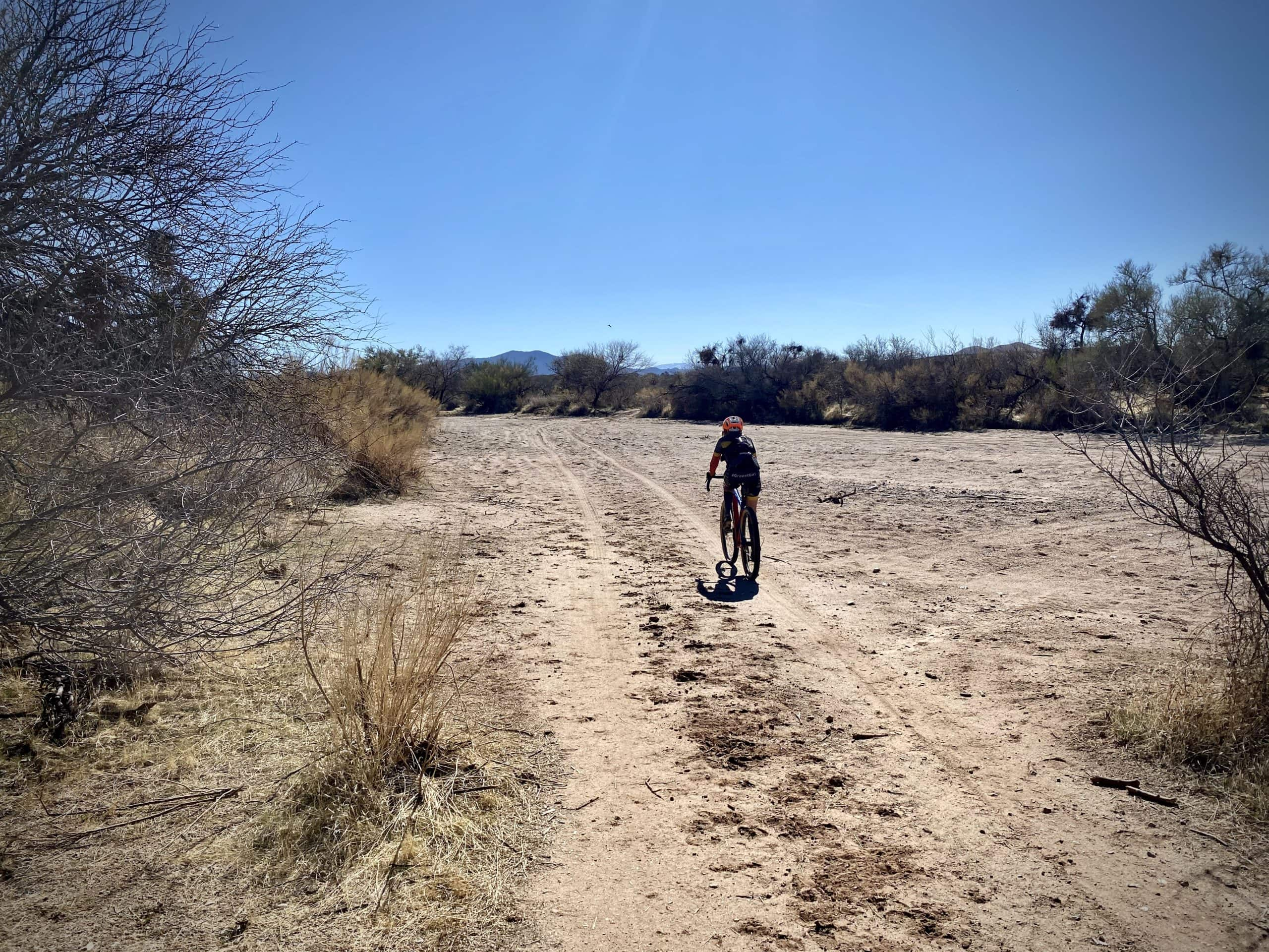 Gravel cyclist riding through a long, sandy was in the Sonoran desert between Tucson and Florence, Arizona.