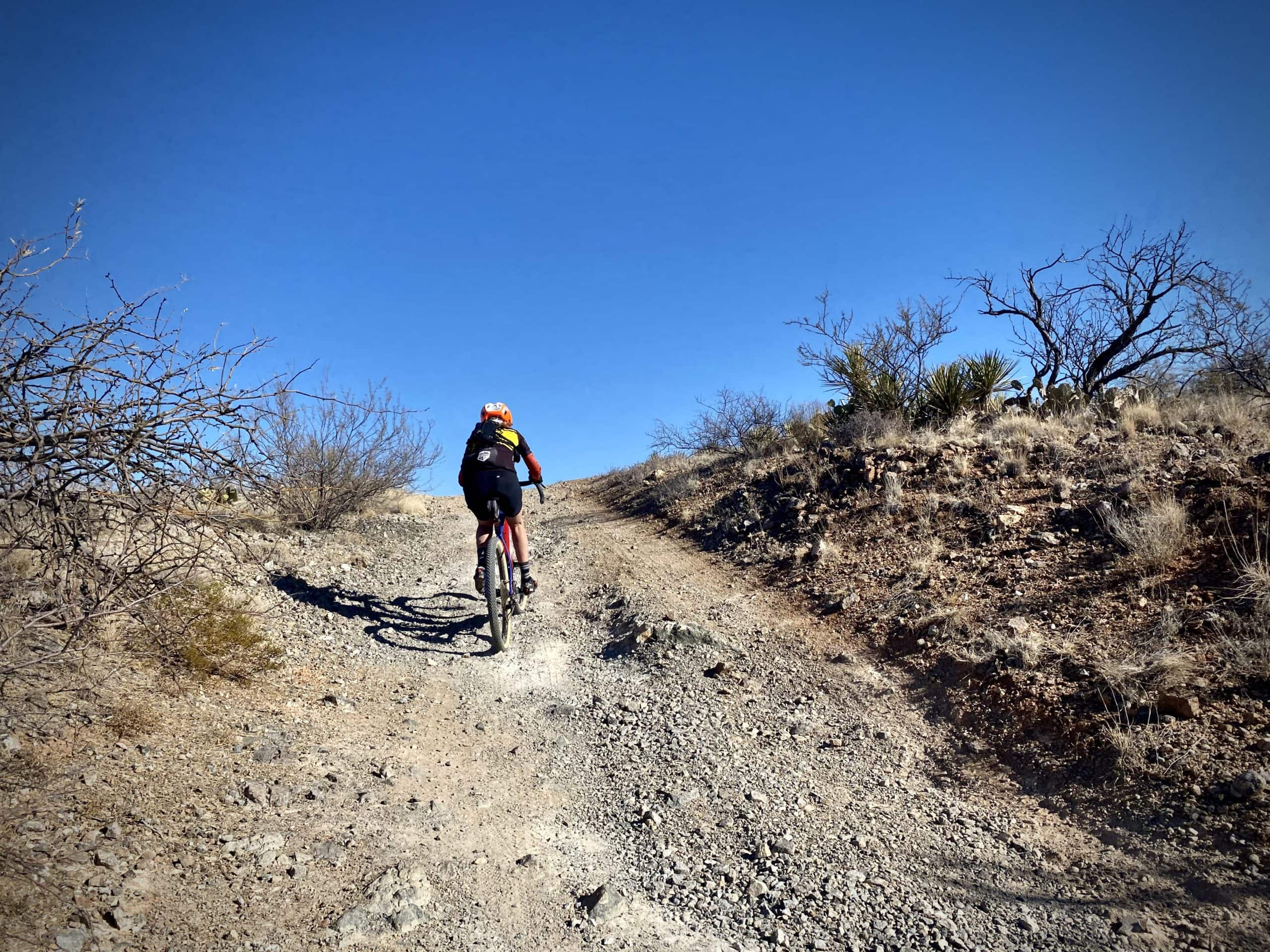 Gravel Girl climbing a rugged, loose section of gravel road.