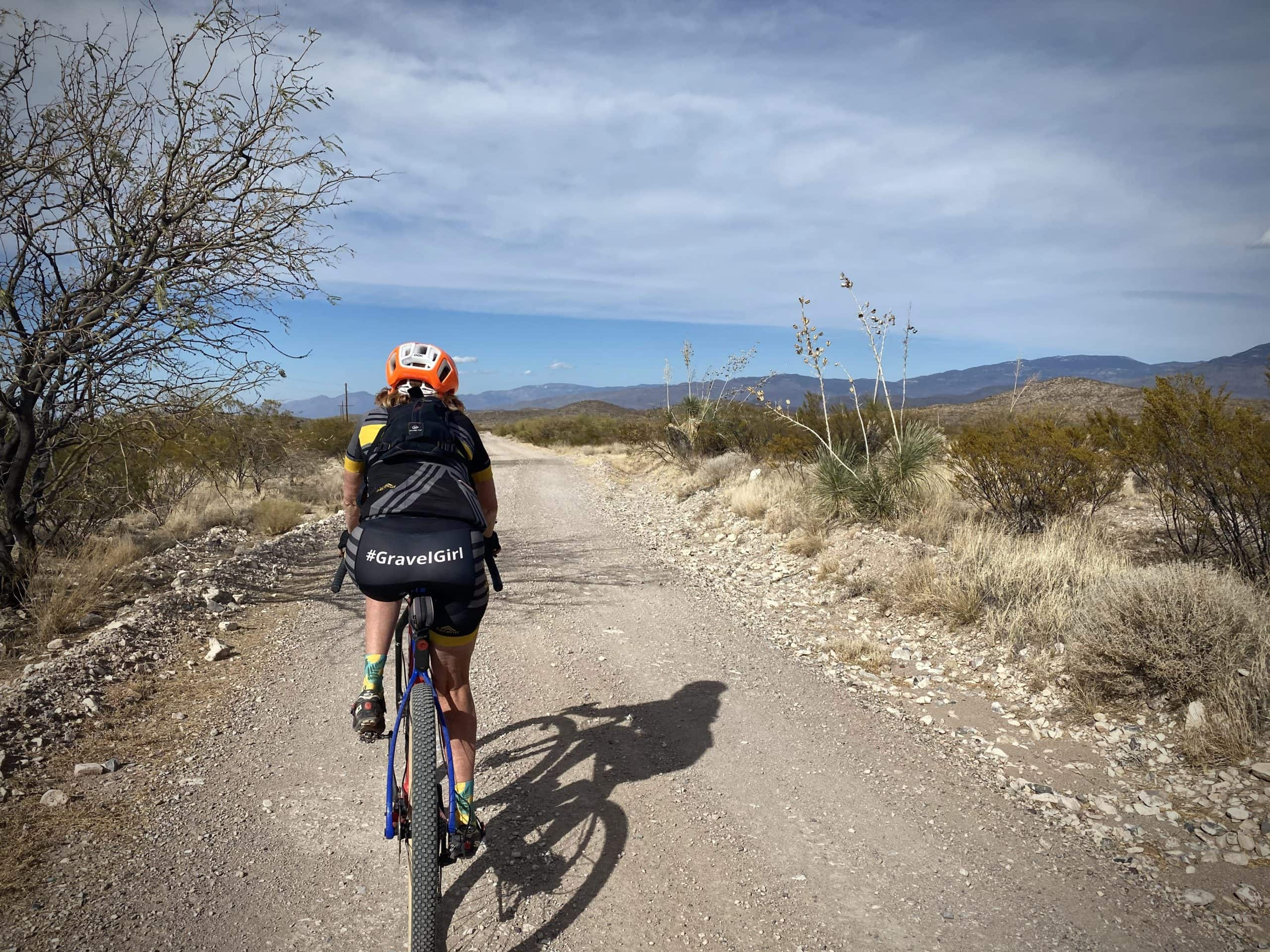 Woman cyclist on gravel road in the Sonoran desert in Arizona.