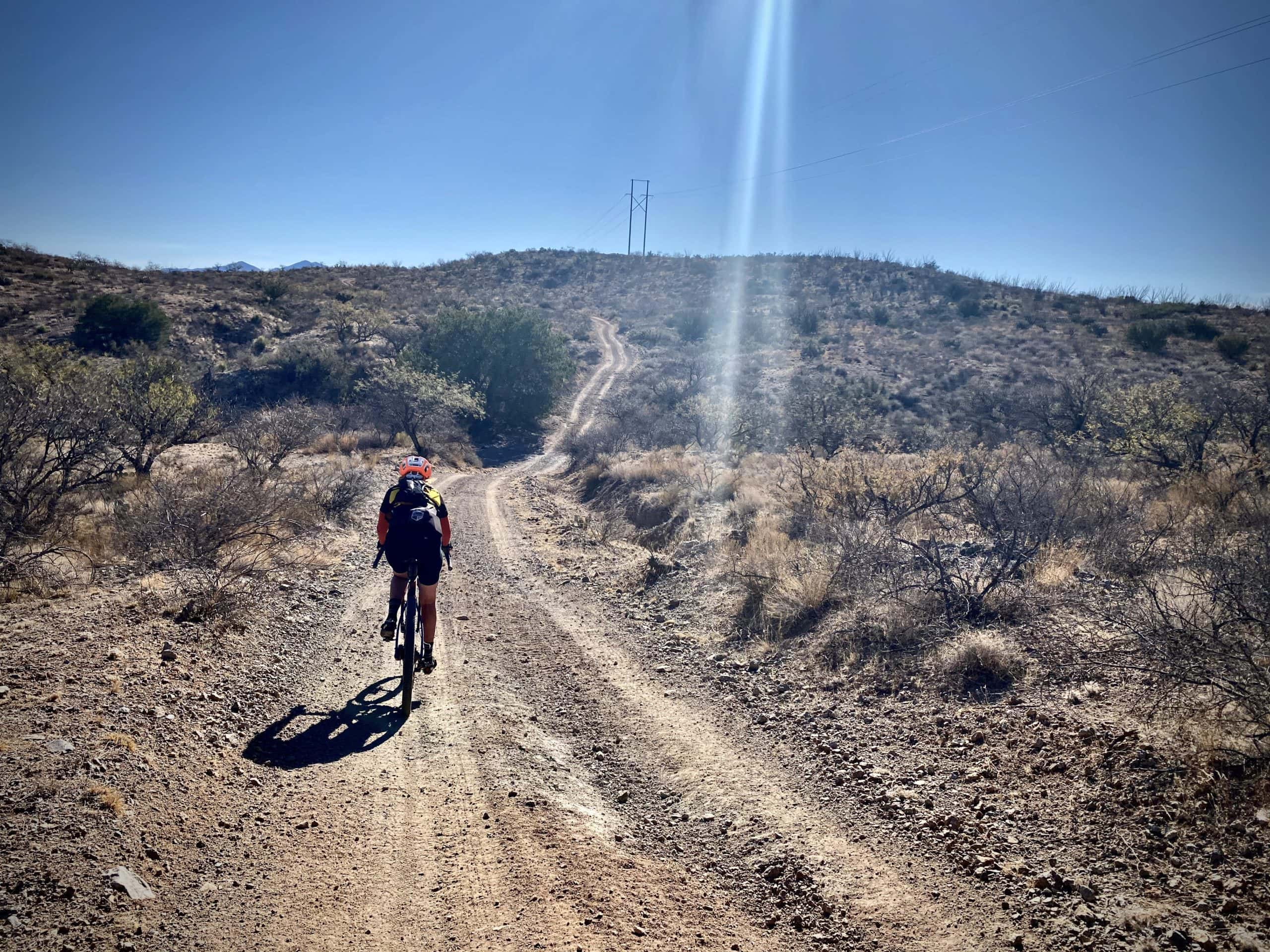 Cyclist on hilly gravel road following a power line in Arizona