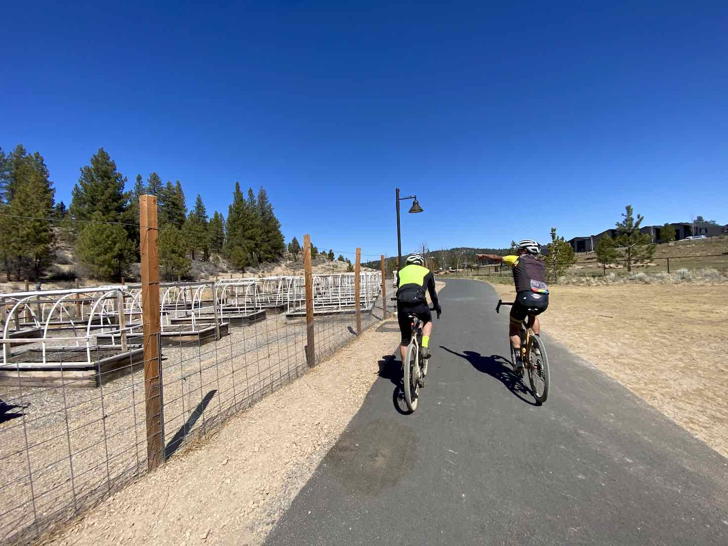 Cyclist on the paved trail near the community gardens at Discovery Park in Bend, Oregon.