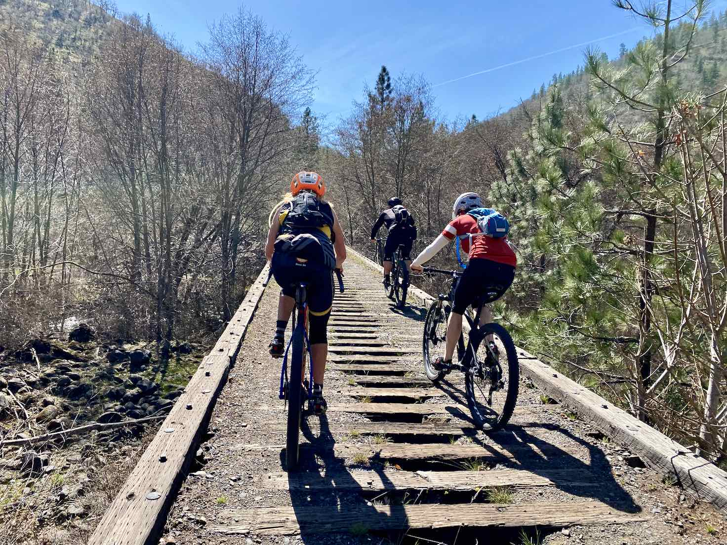 Cyclists crossing over an old railroad trestle bridge on the Klickitat Trail.